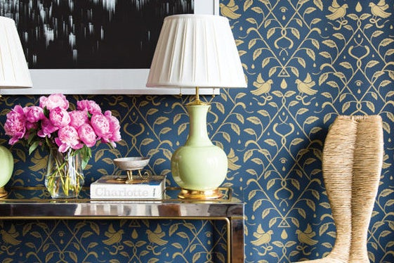 console table in front of blue and gold wallpaper