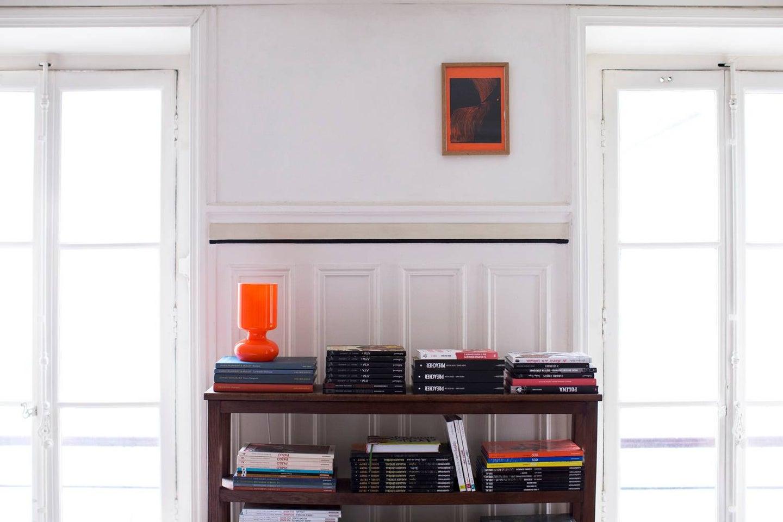 parisian interiors white wall with orange lamp