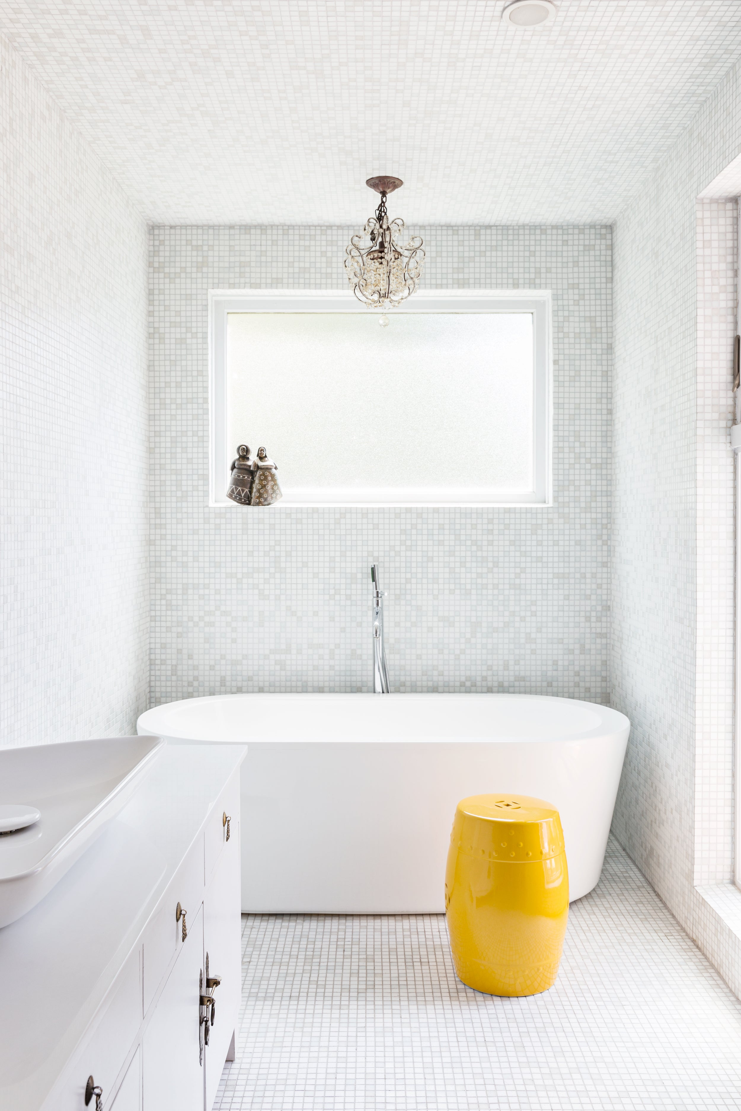 a bathroom decorated with tiny white tiles