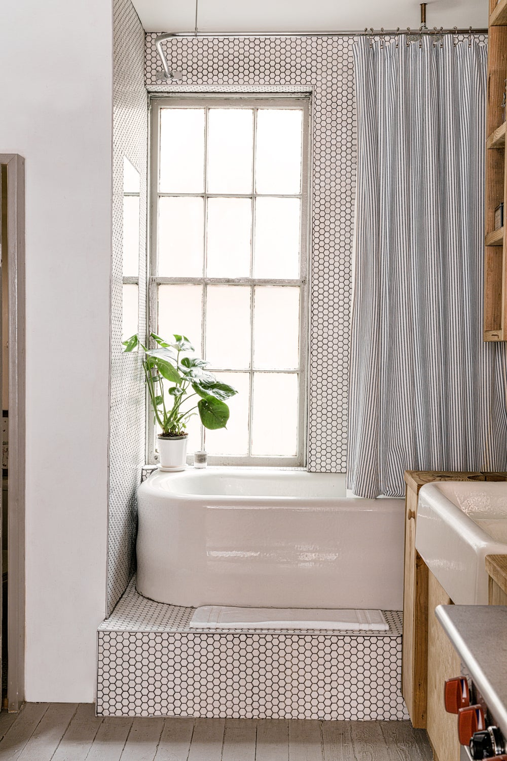 a white bathroom that is conveniently located right off of the kitchen