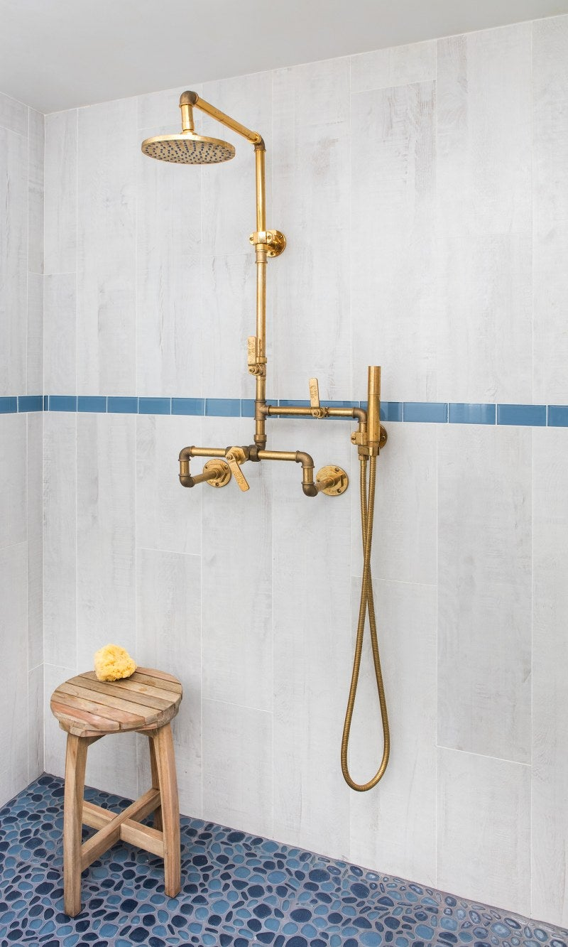 a bathroom designed with gold exposed piping