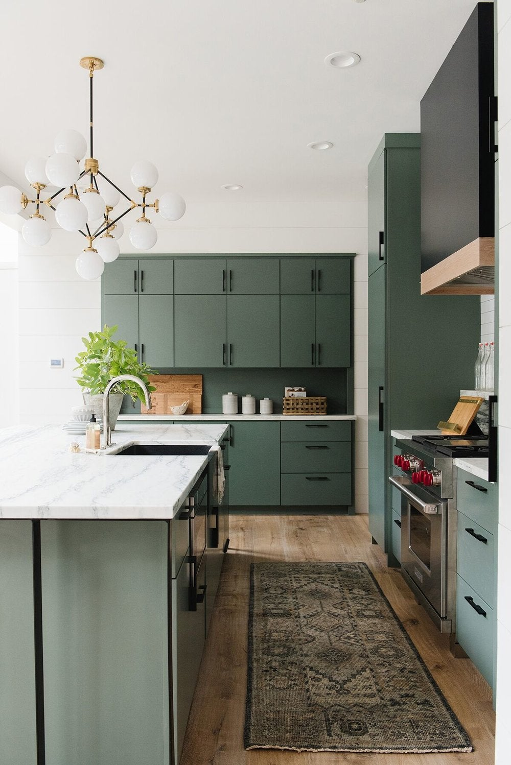 large kitchen with green cabinets and black hardware