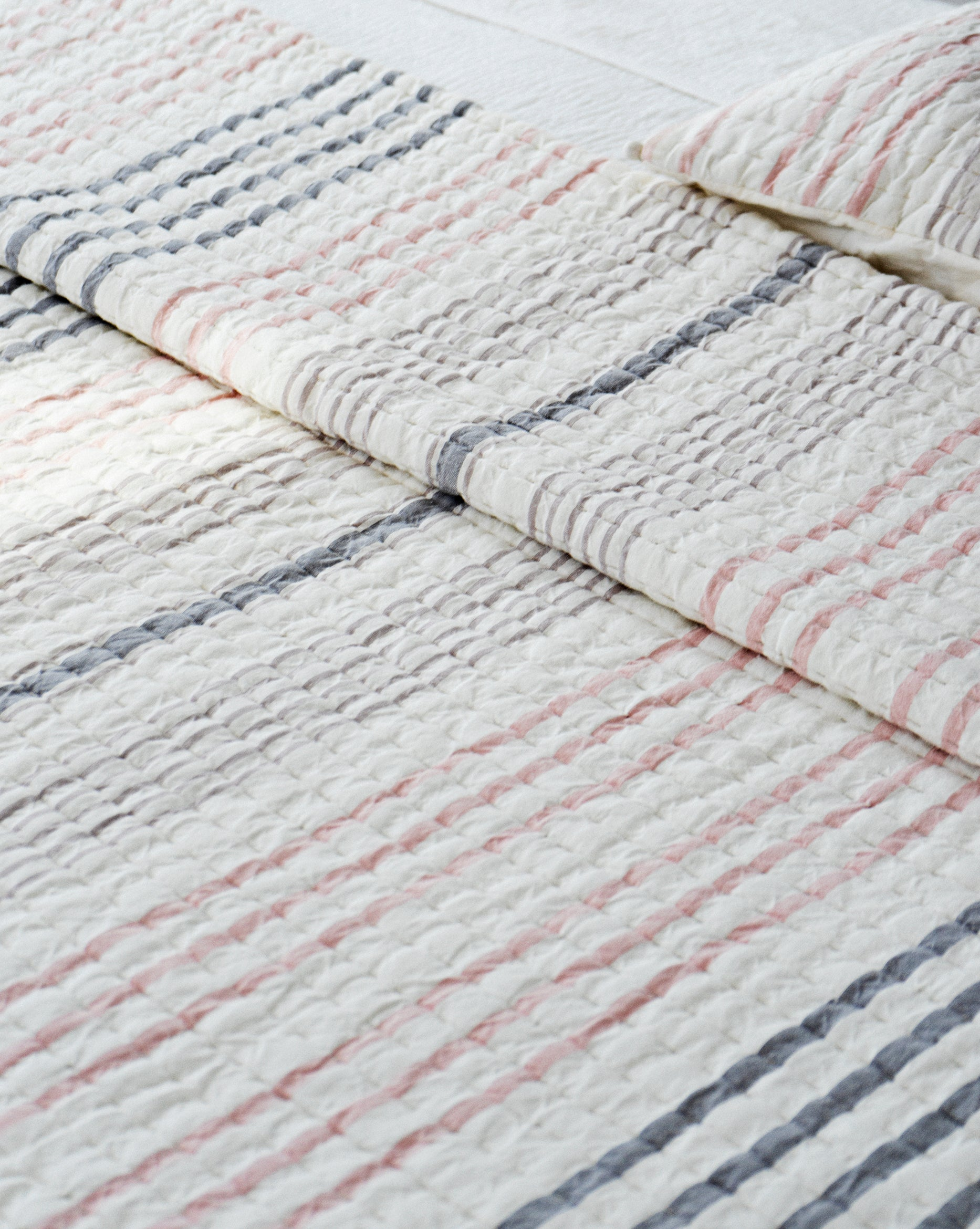 White quilt with pink and gray stripes.