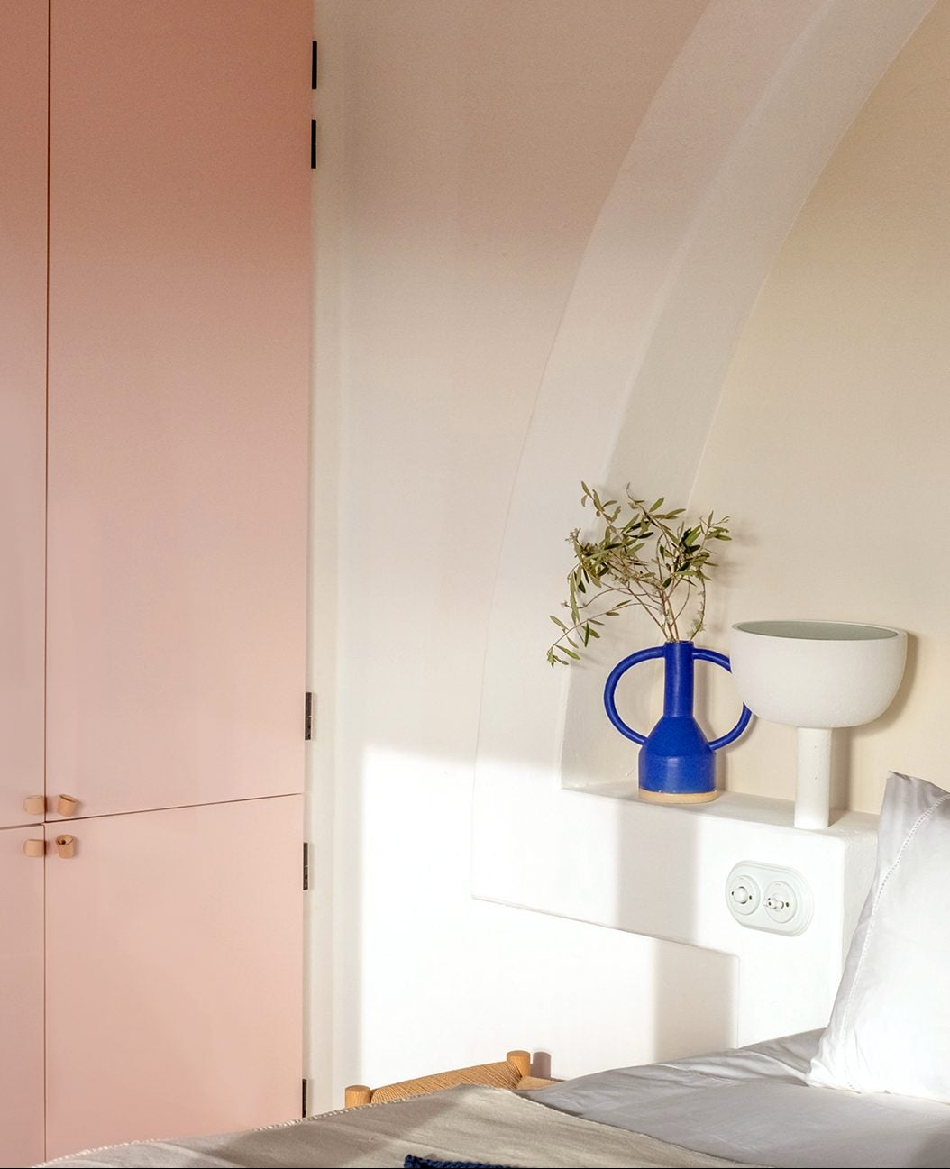 bed with blue-green headboard and pink cabinets