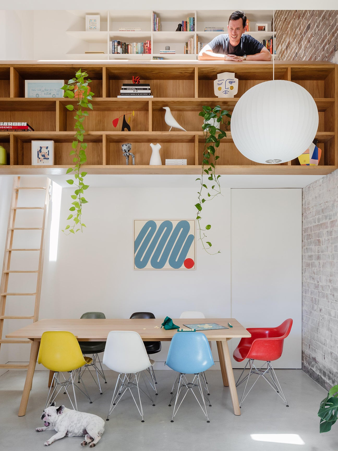 lofted office over dining table with man looking down