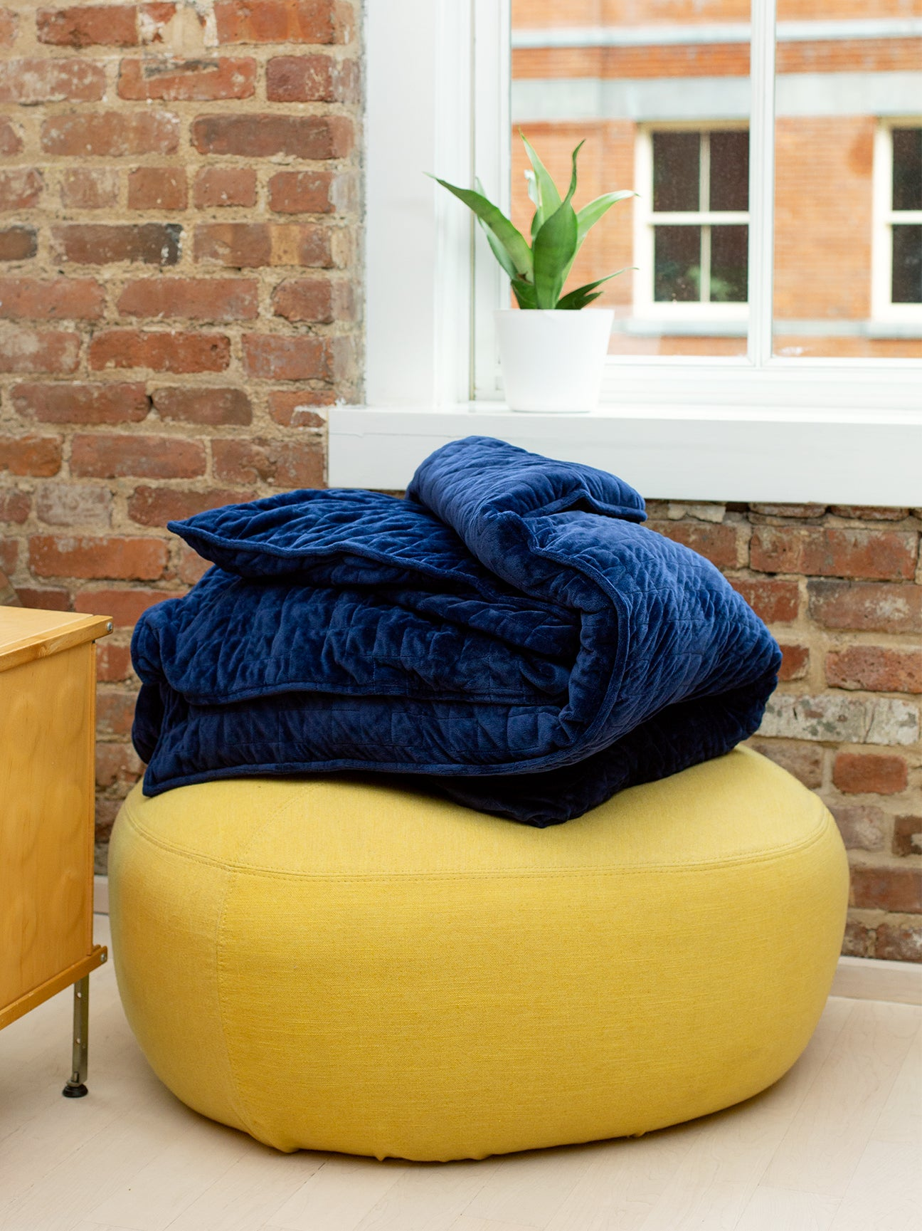 Yellow pouf with blue blanket.
