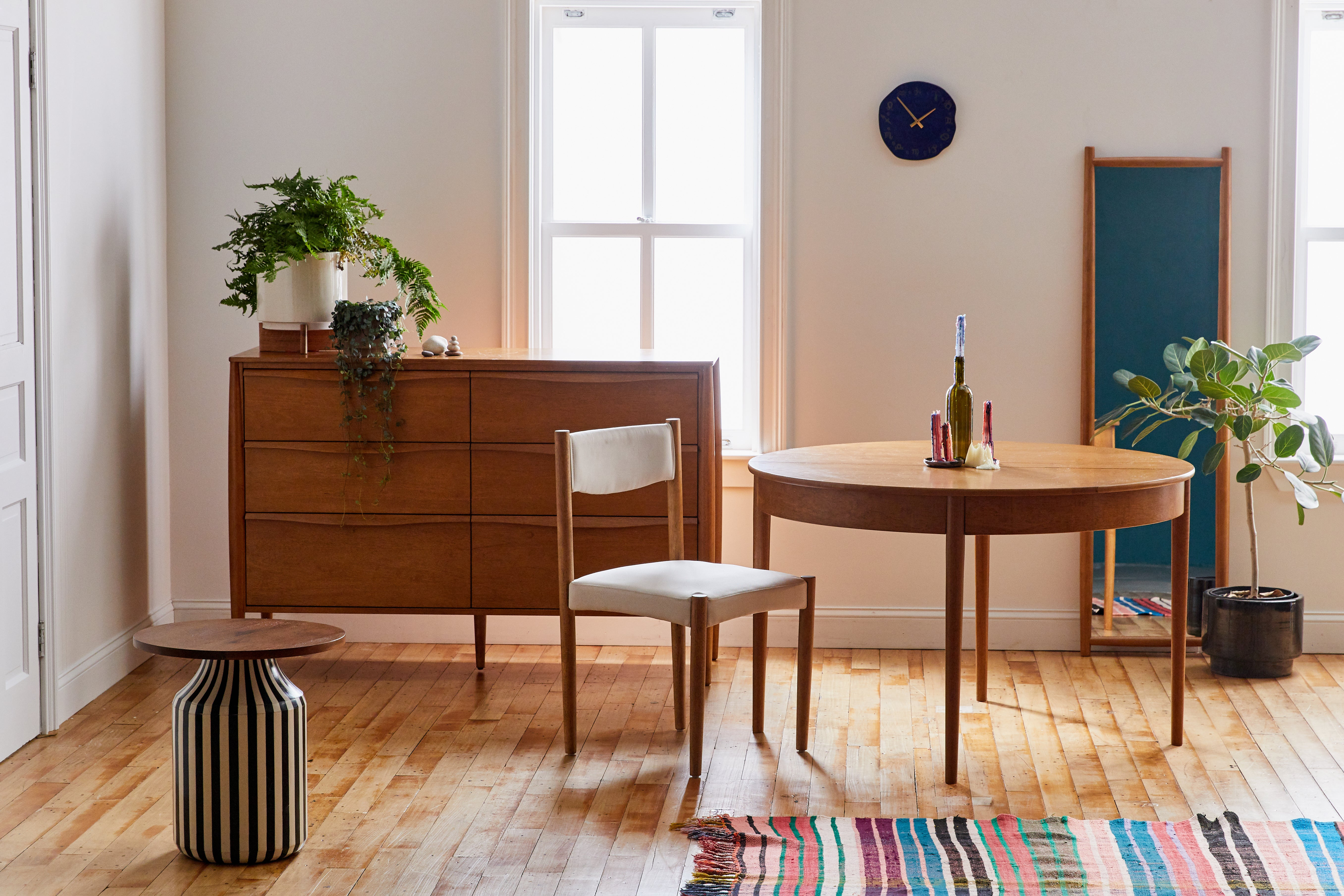 Dining room with midcentury style table and chairs, credenza, floor mirror, and colorful striped rug