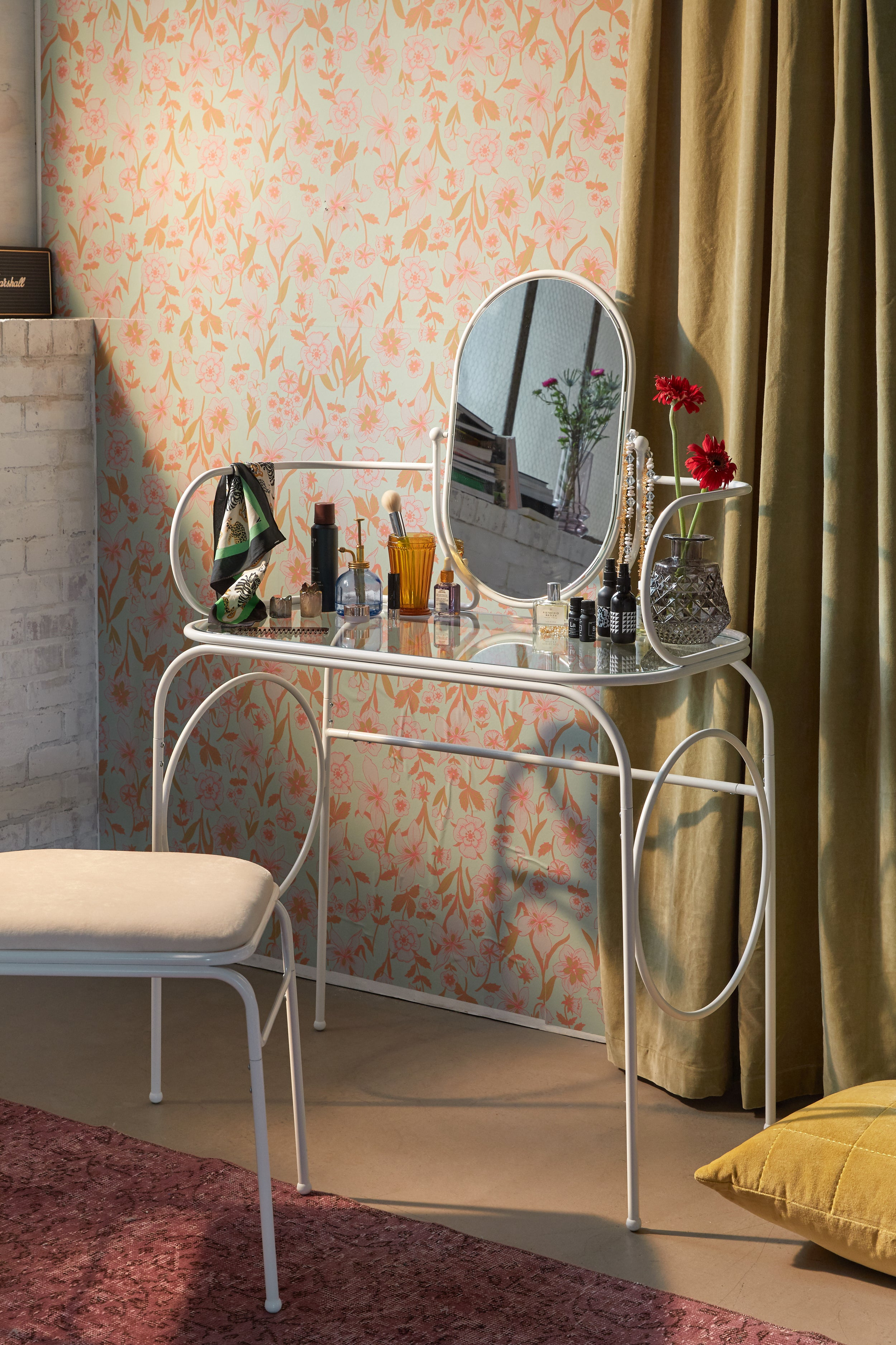 A white vanity made from bent steel tubing with matching mirror and stool