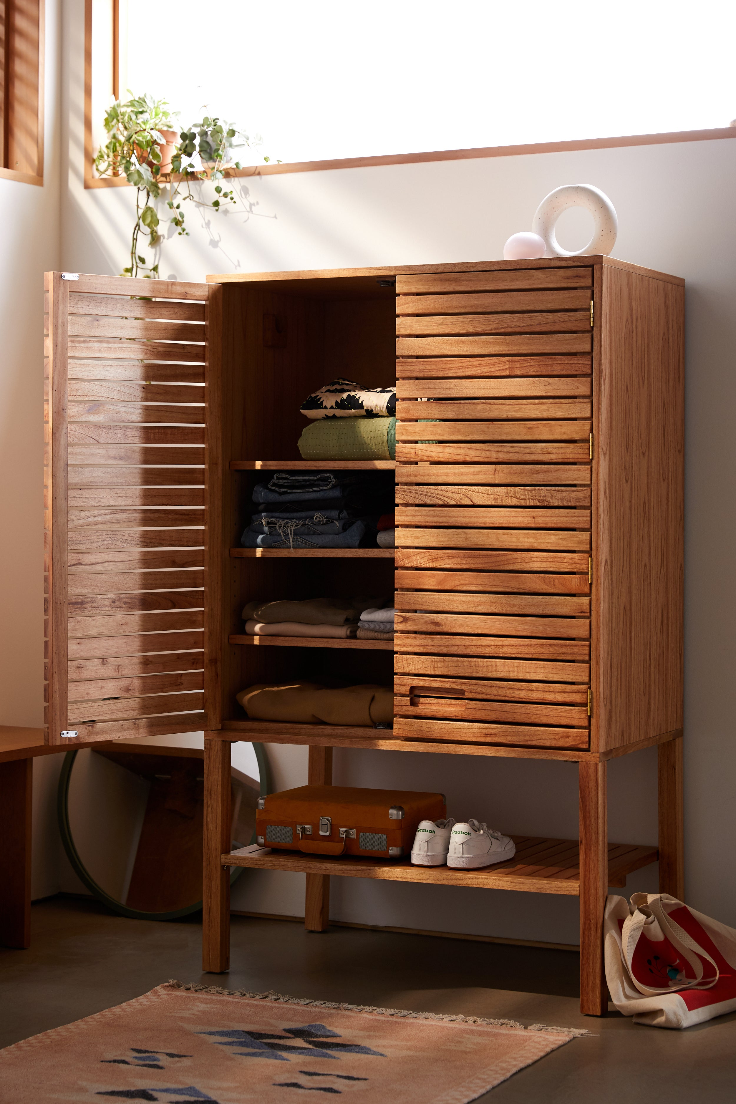 A slatted wood armoire with one door open and shoes on a bottom shelf