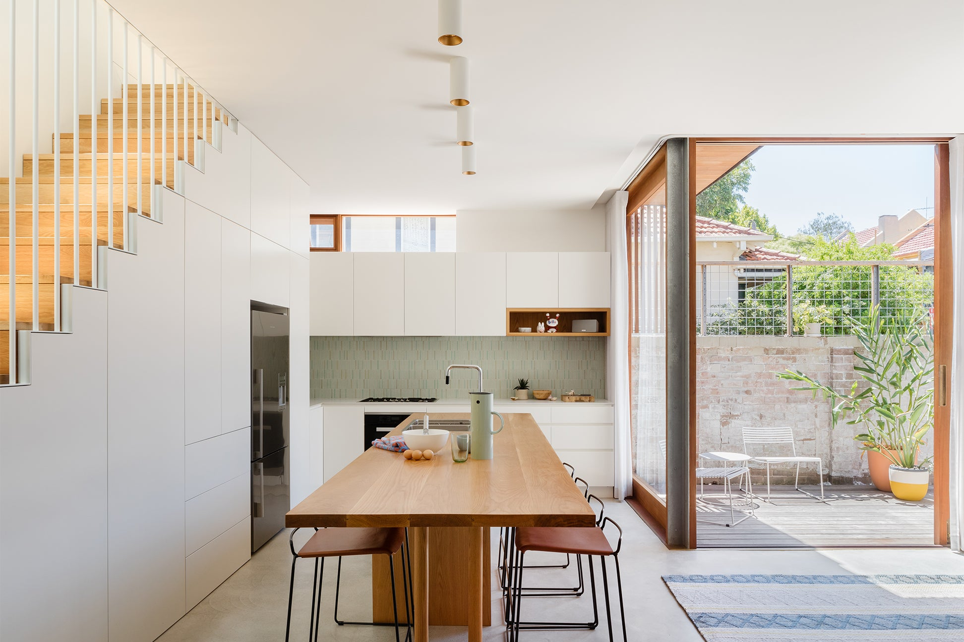 modern kitchen with white cabinetry and an oak wood open shelf cubby