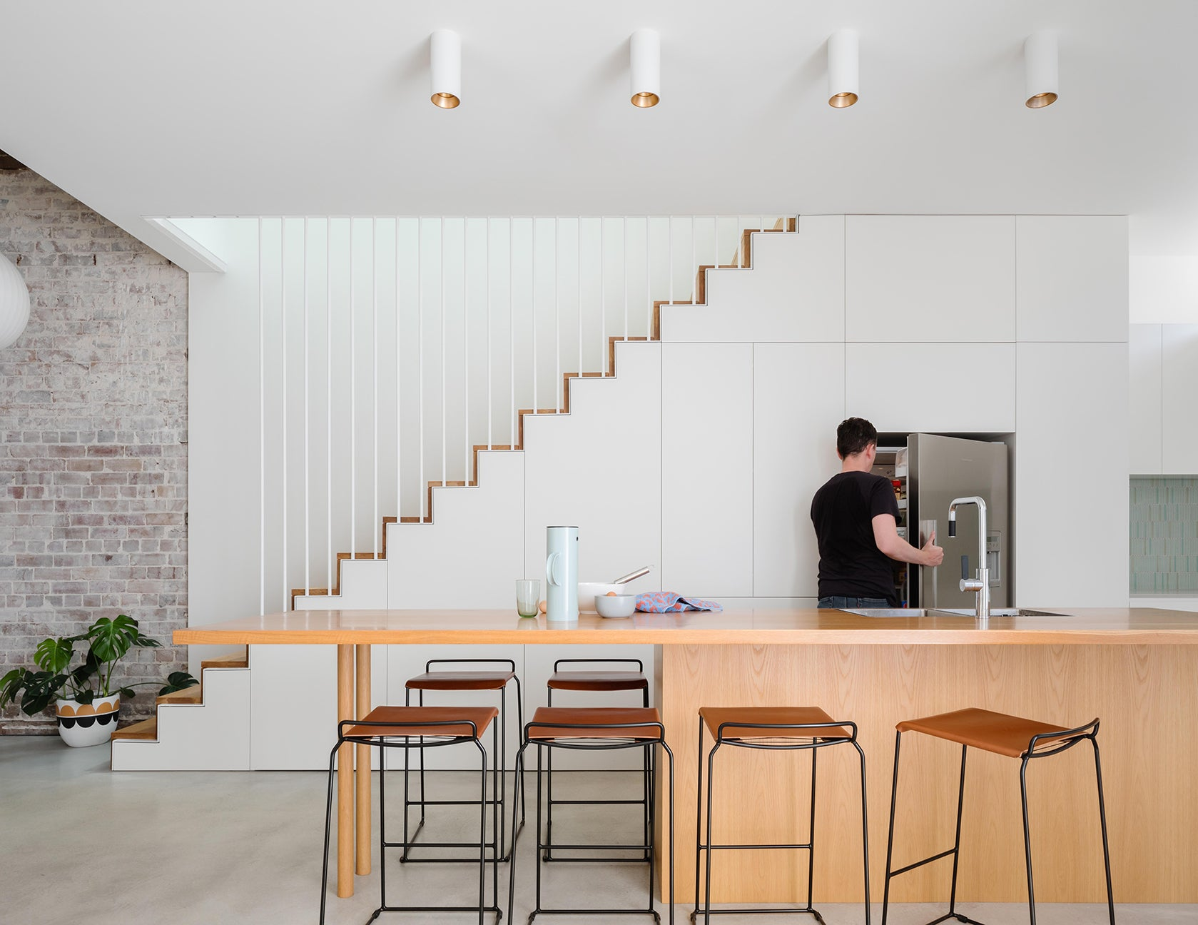 white kitchen cabinetry beneath steel staircase