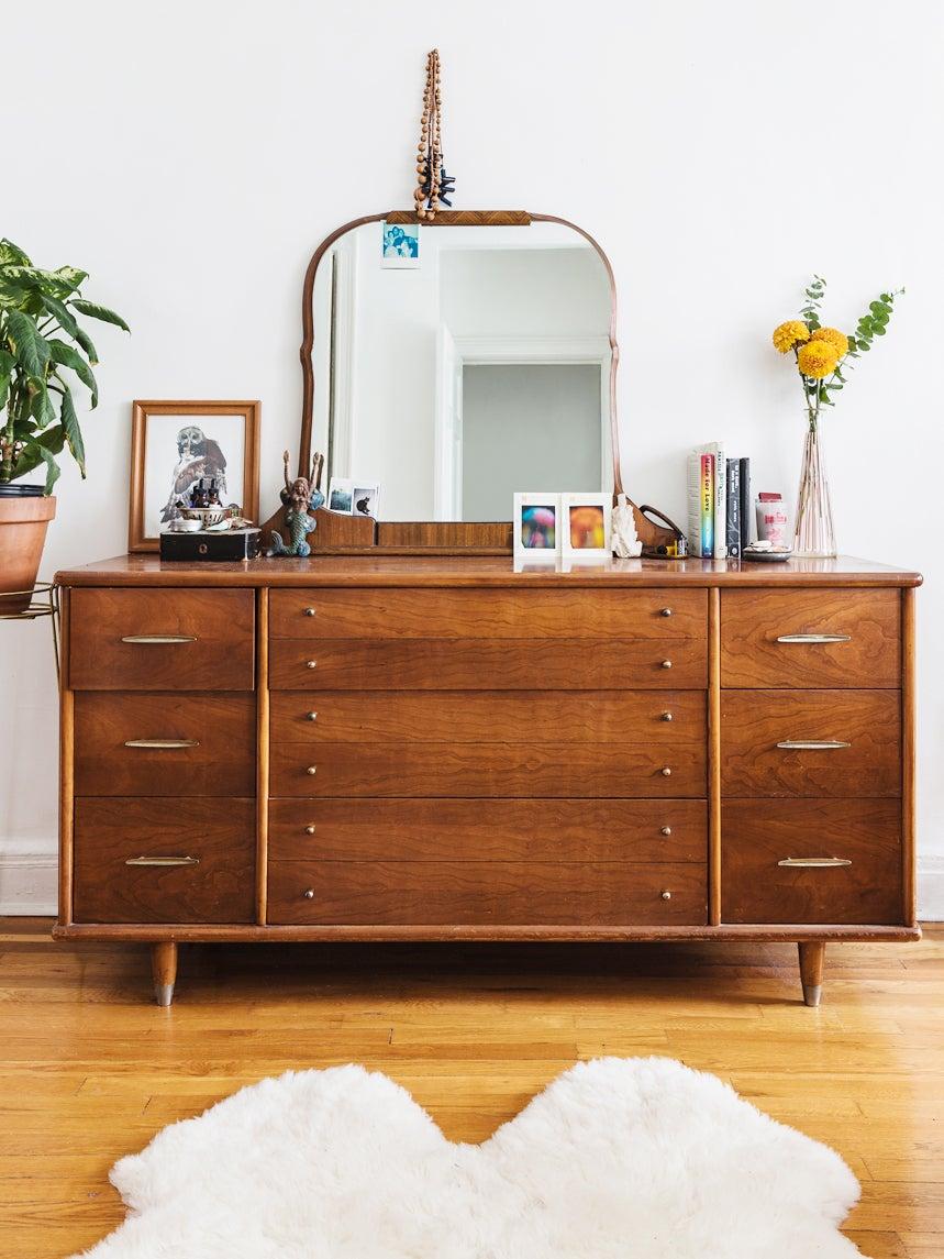 vintage wood dresser with vanity mirror leaning on it