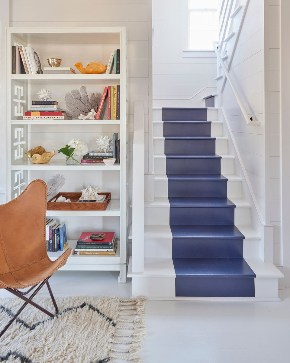 white beach house with blue painted stripe down the stairs
