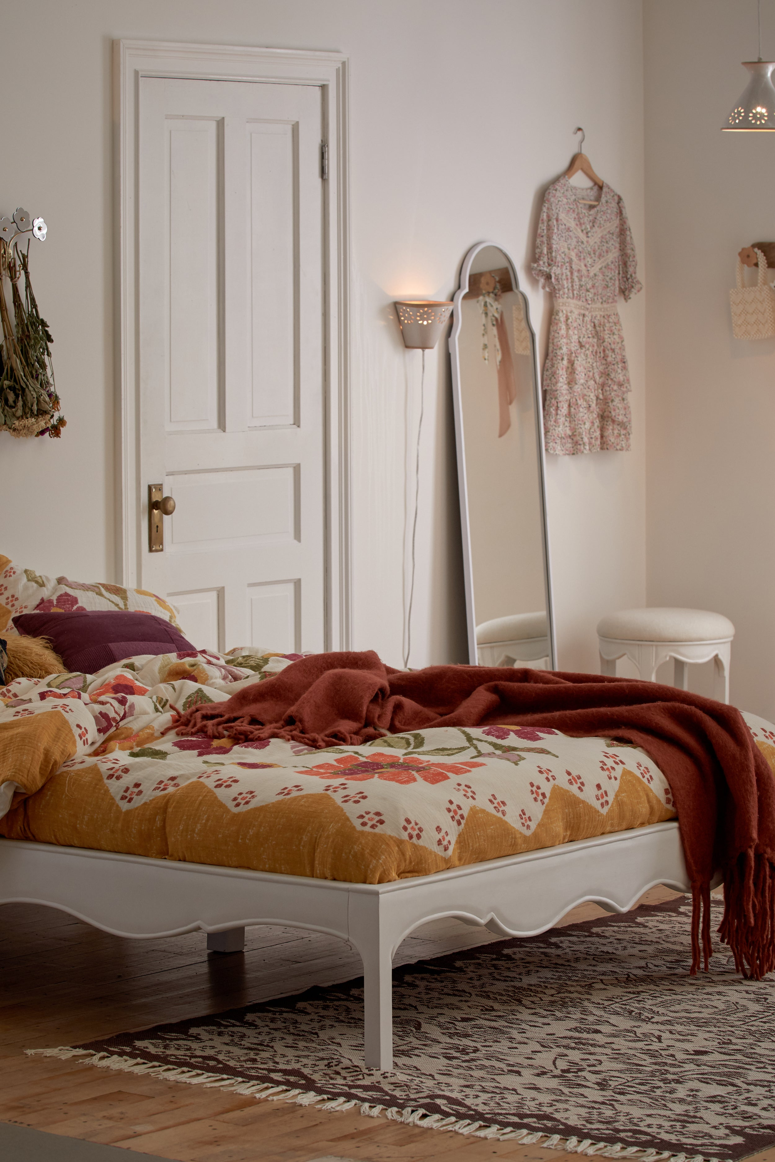 white bed with yellow sheets and red blanket