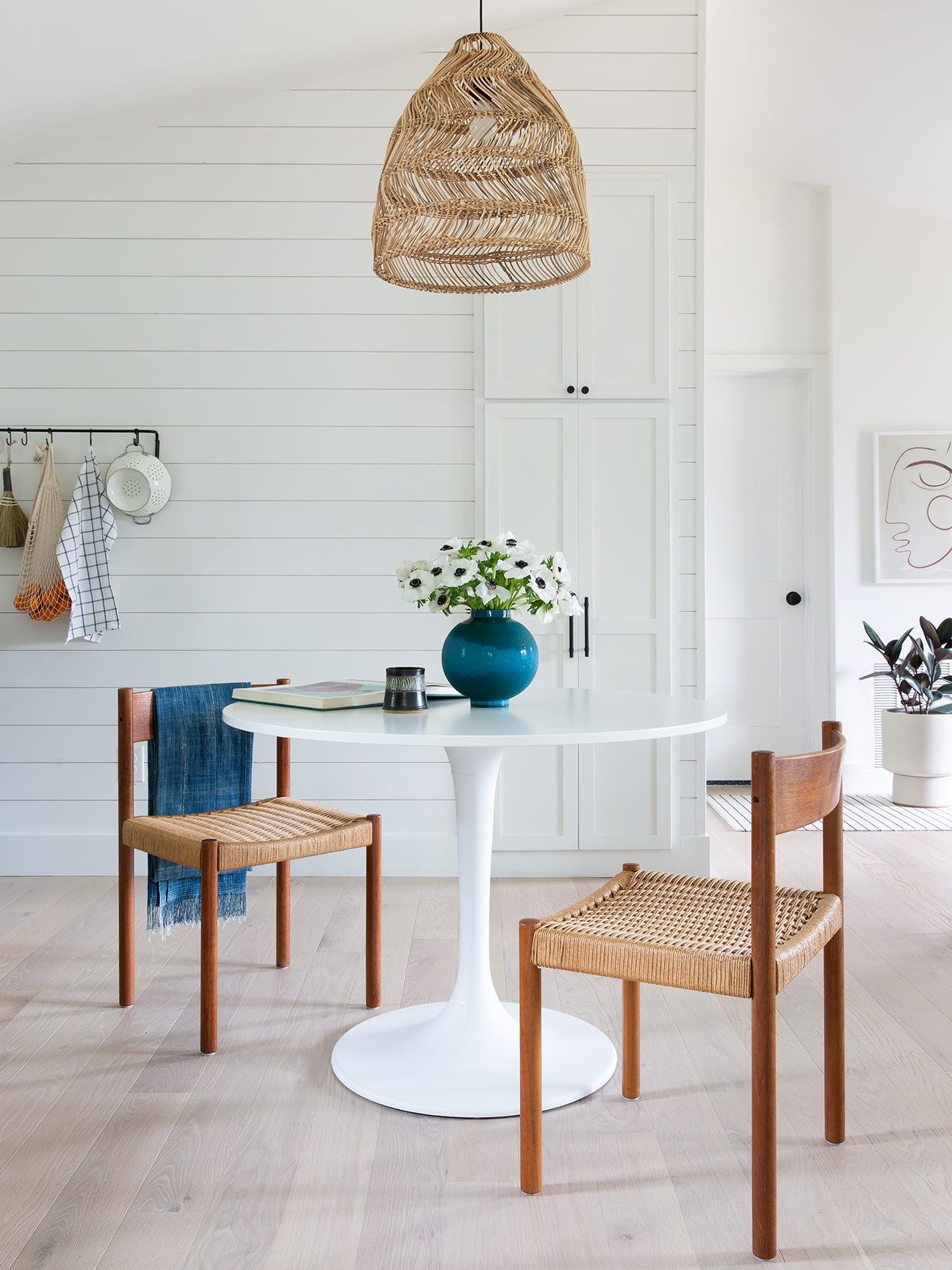 White circle dining table with blue flower vase.