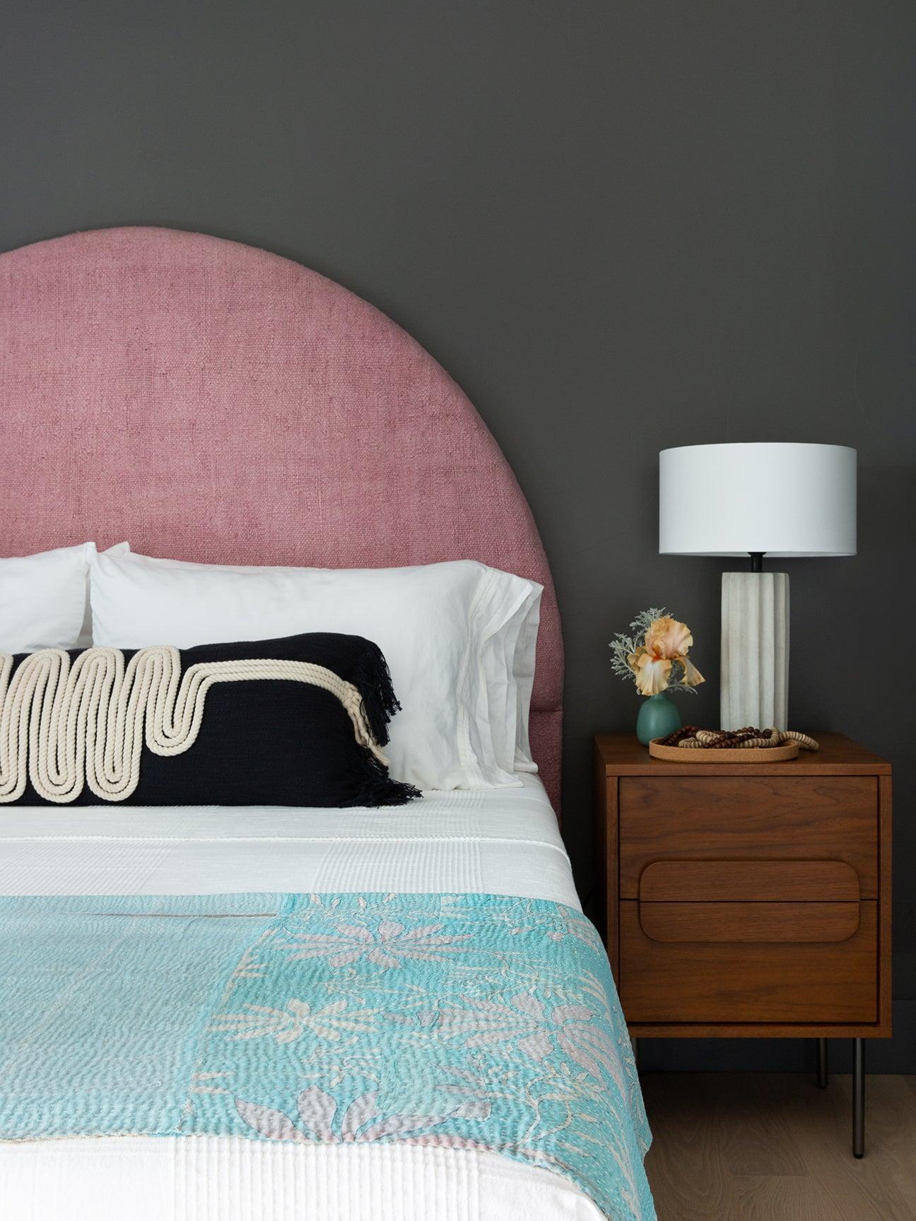 Dark gray bedroom with pink headboard.