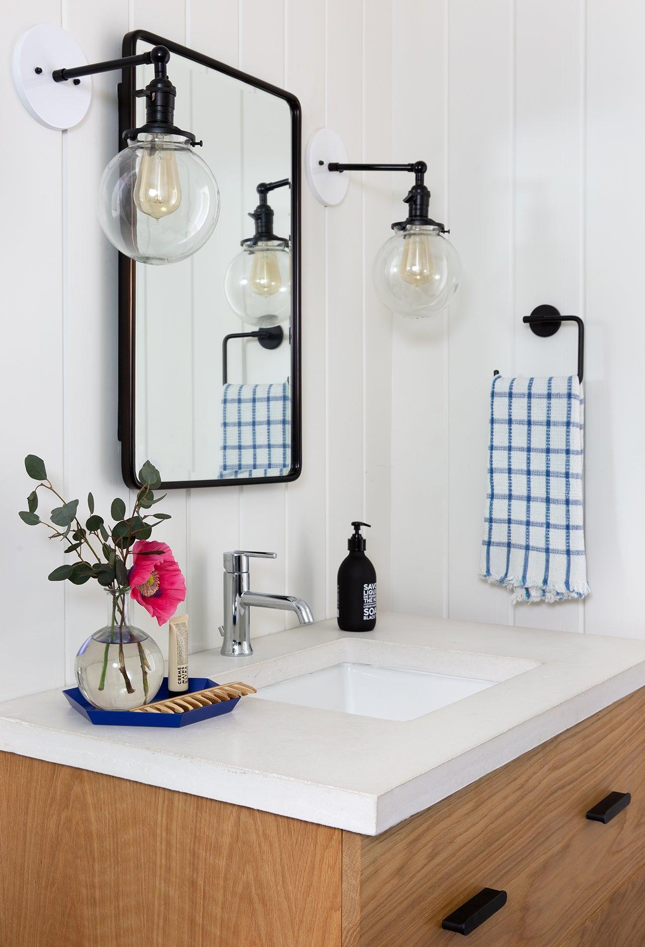 Bathroom sink with large bulb sconces.