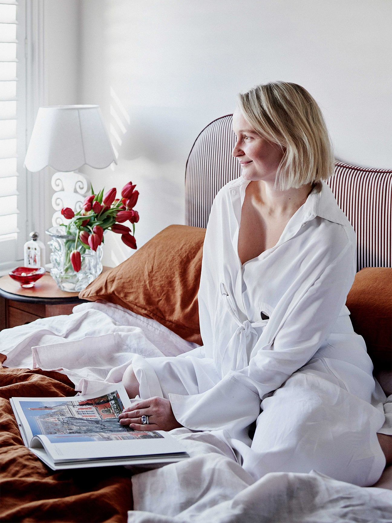Woman on bed in white bathrobe.