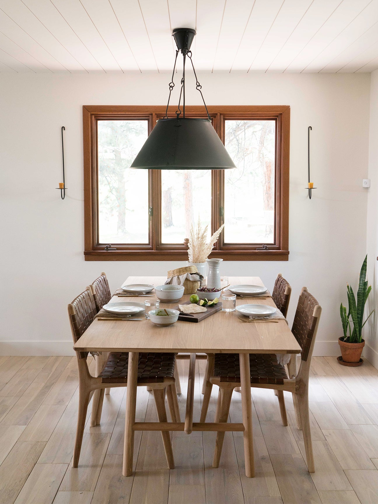 neutral dining room with farmhosue table and black pendant