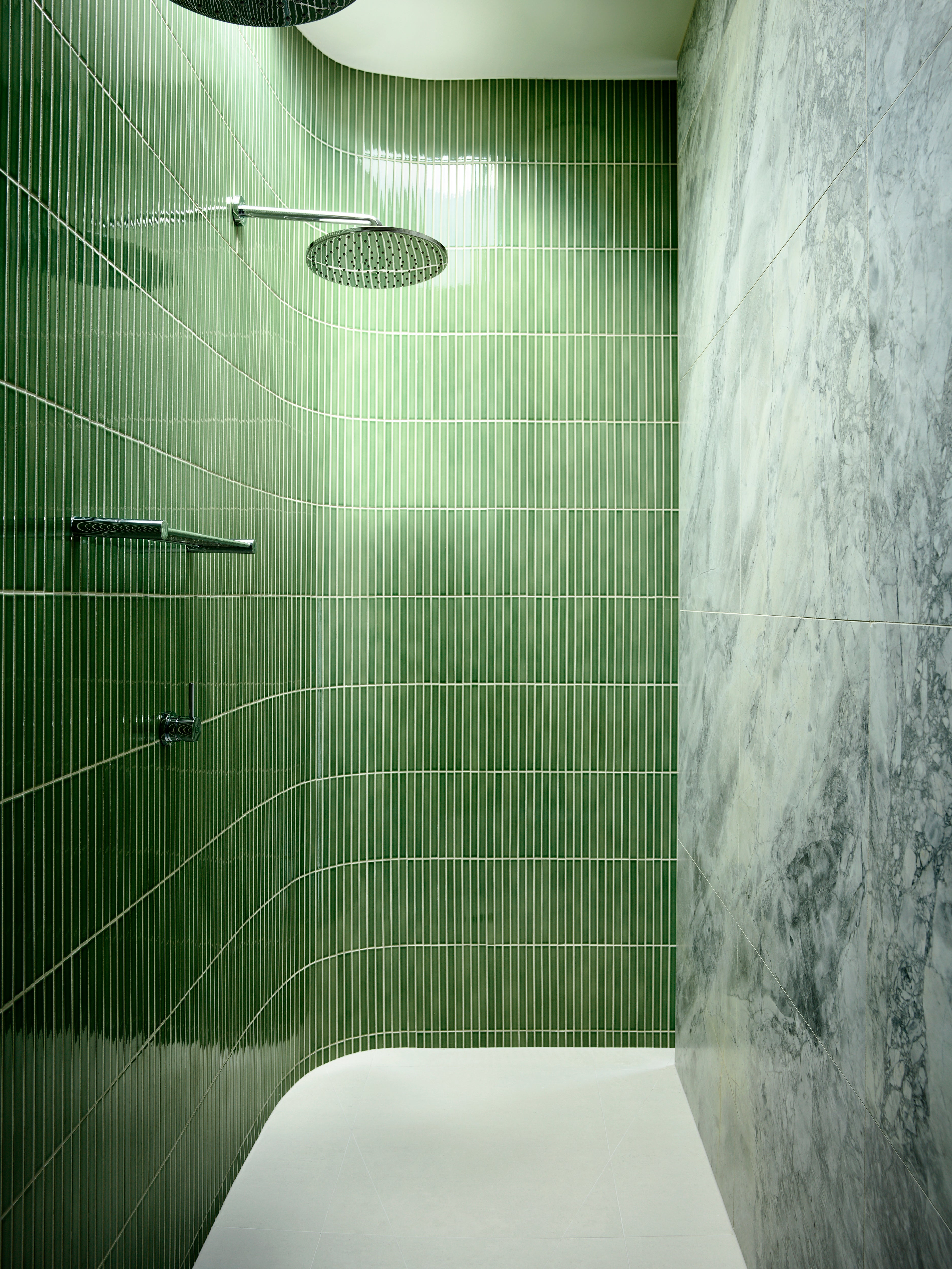 curved shower with long narrow green tiles