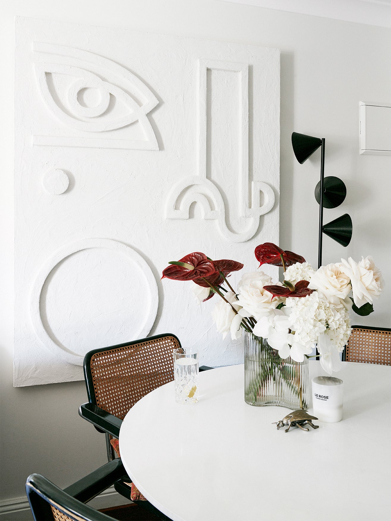 White coffee table with white artwork on walls.