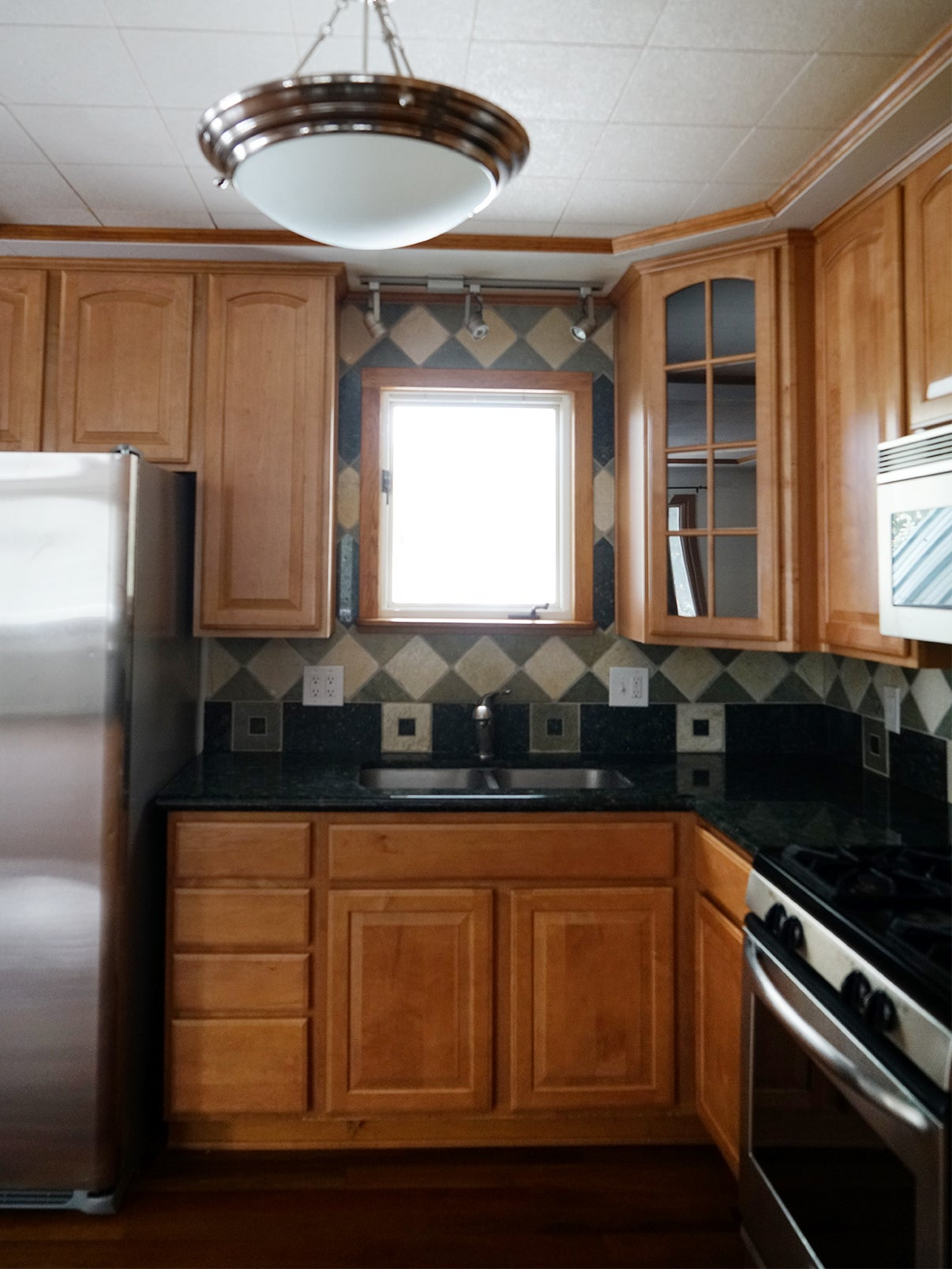 before image of a kitchen with brown cabinets and black counters