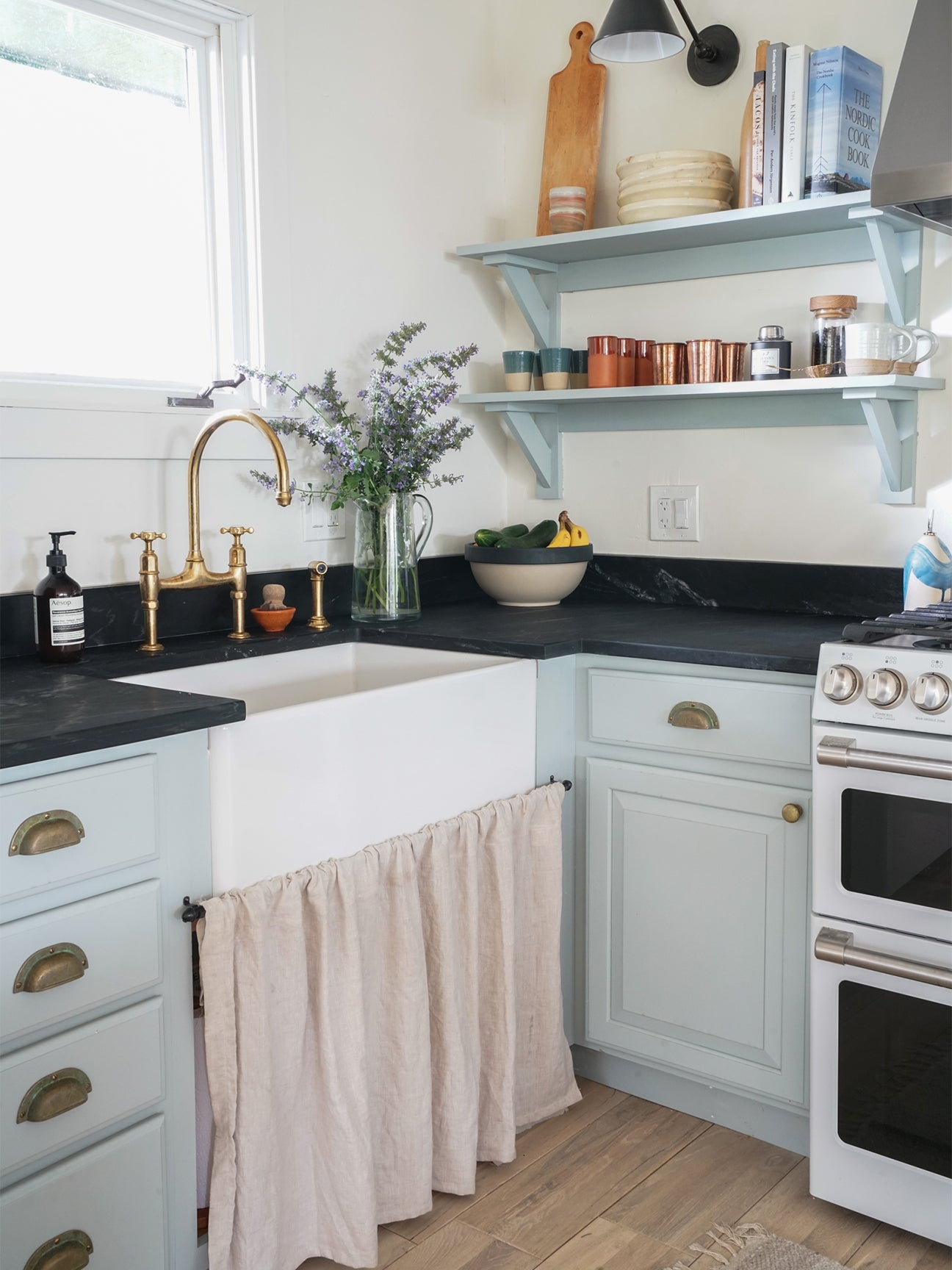 farmhouse kitchen sink with linen curtain below
