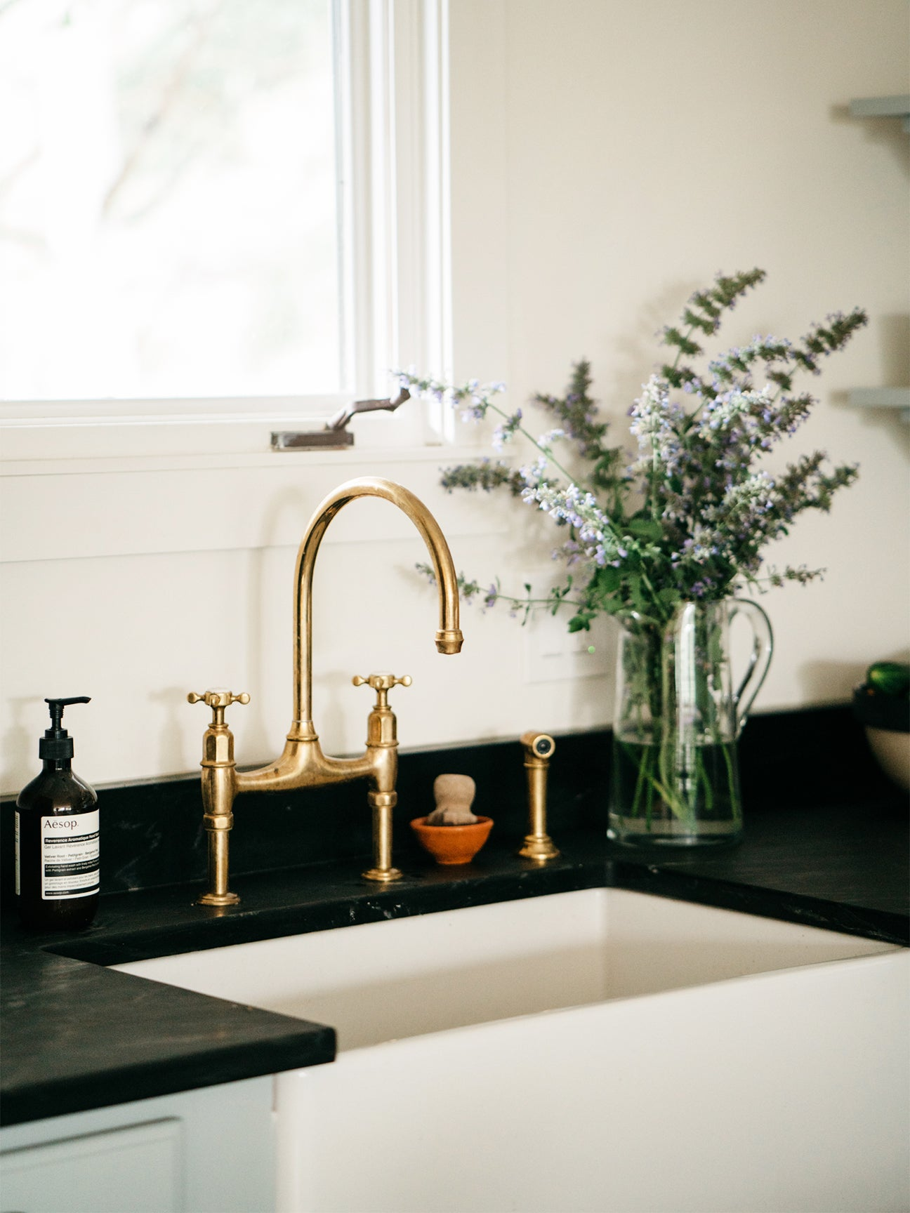 close up shot of a kitchen farmhouse sink with brass faucet