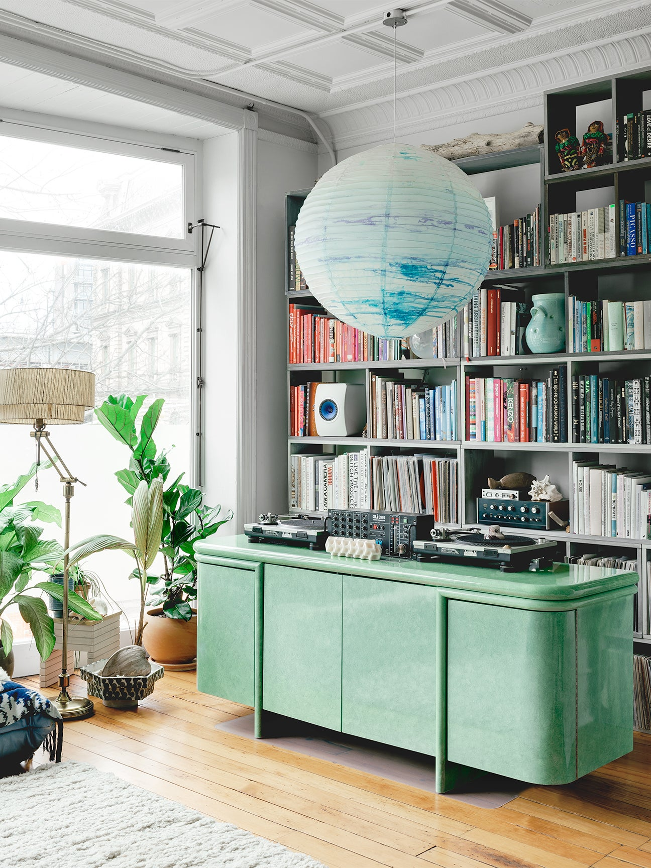 Room with green console and colorful bookshelf.