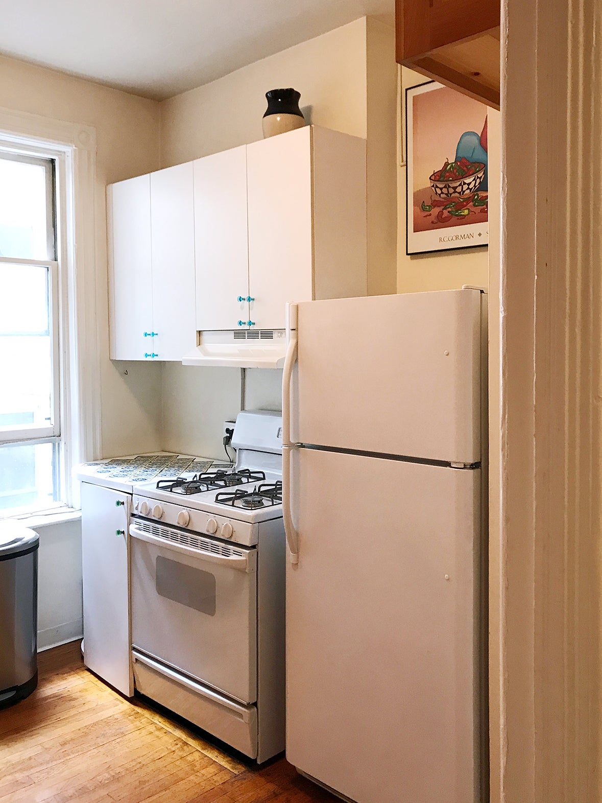 small kitchen with white fridge, oven, and cabinets