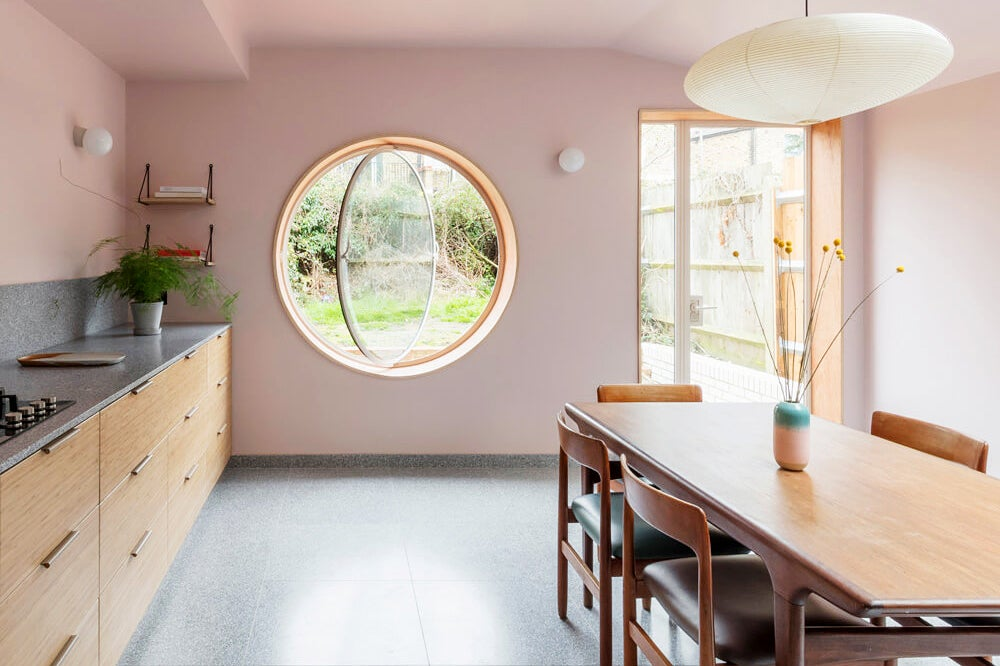 pink kitchen and dining room with an open round window
