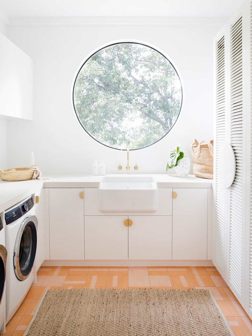 round window in a white laundry room with orange and pink tiles