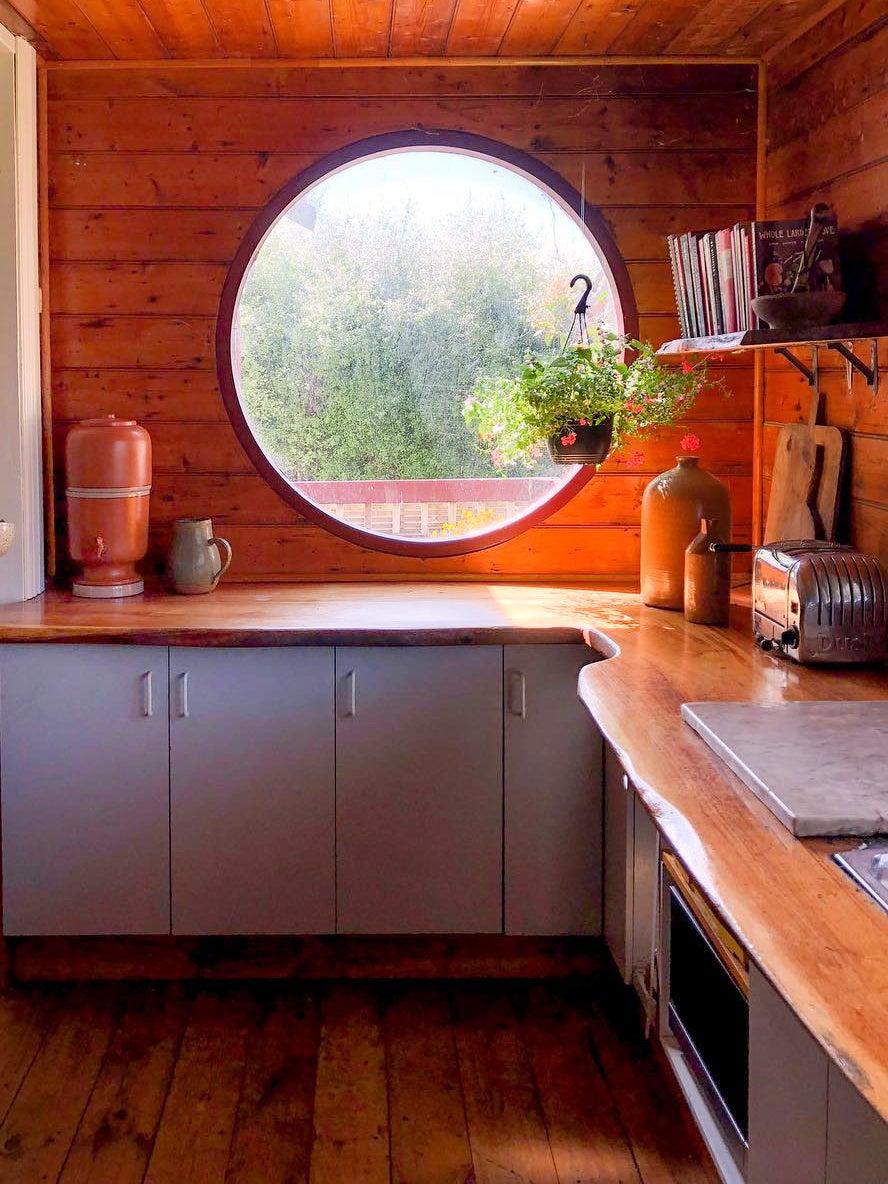 cozy cabin kitchen wiht a round window