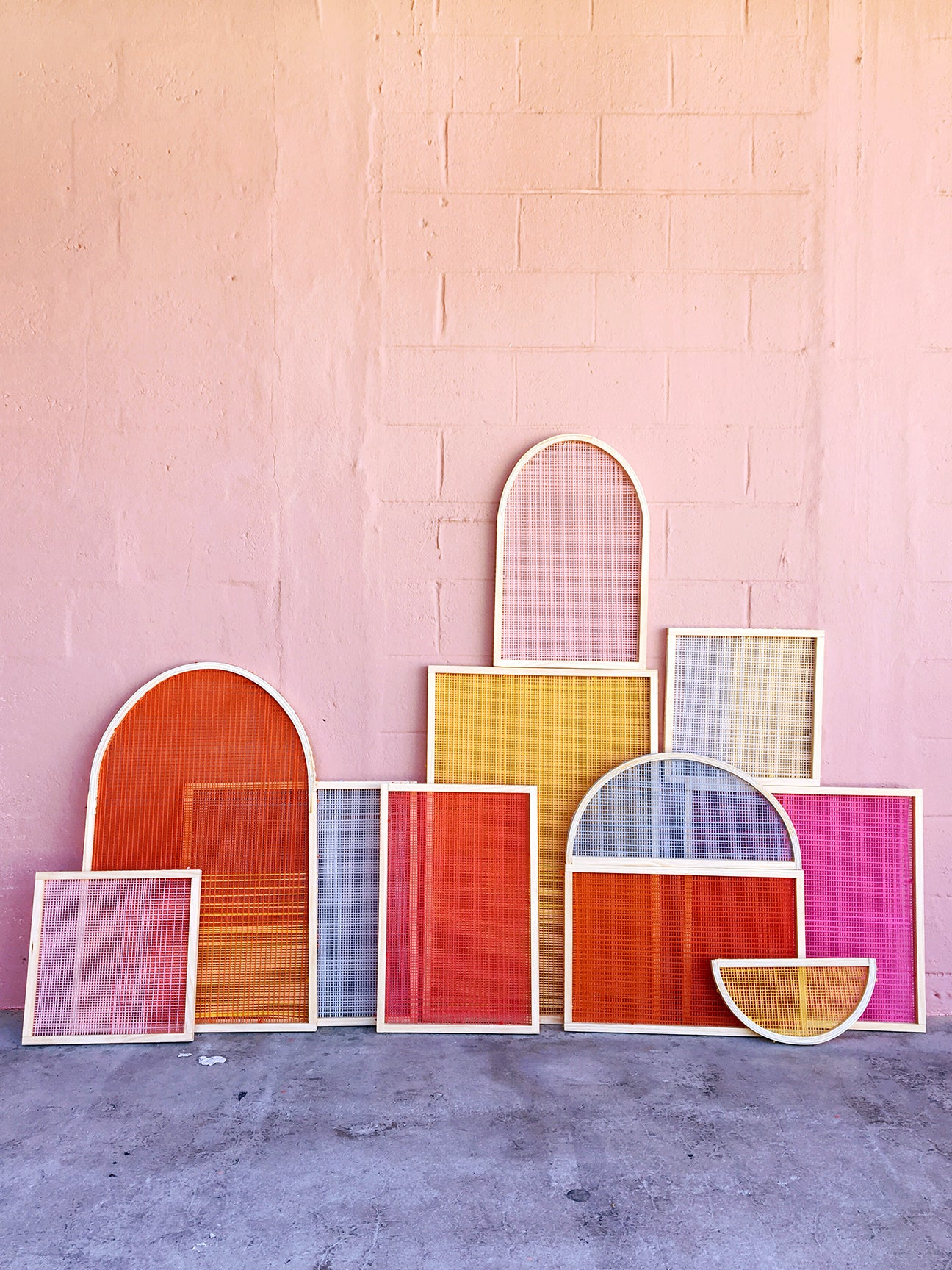 colorful woven wall hangings leaning against a pink exterior wall