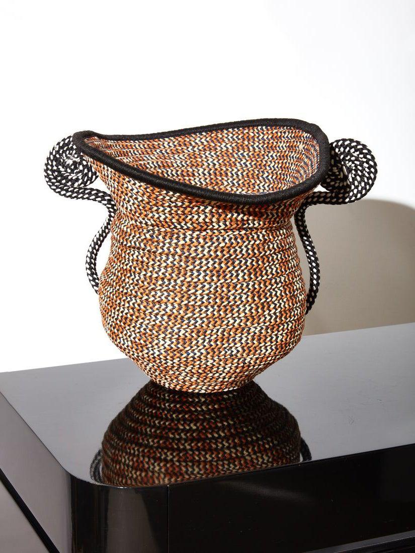 a braided cord urn sitting on a black table