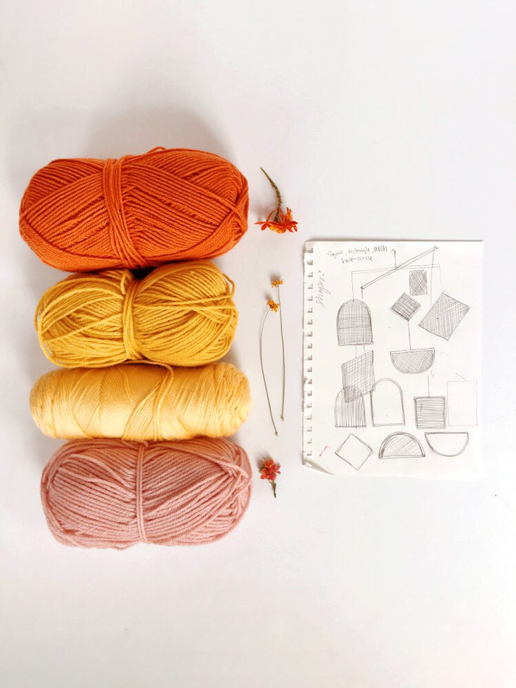 bunches of colorful yarn sitting next to a sketch