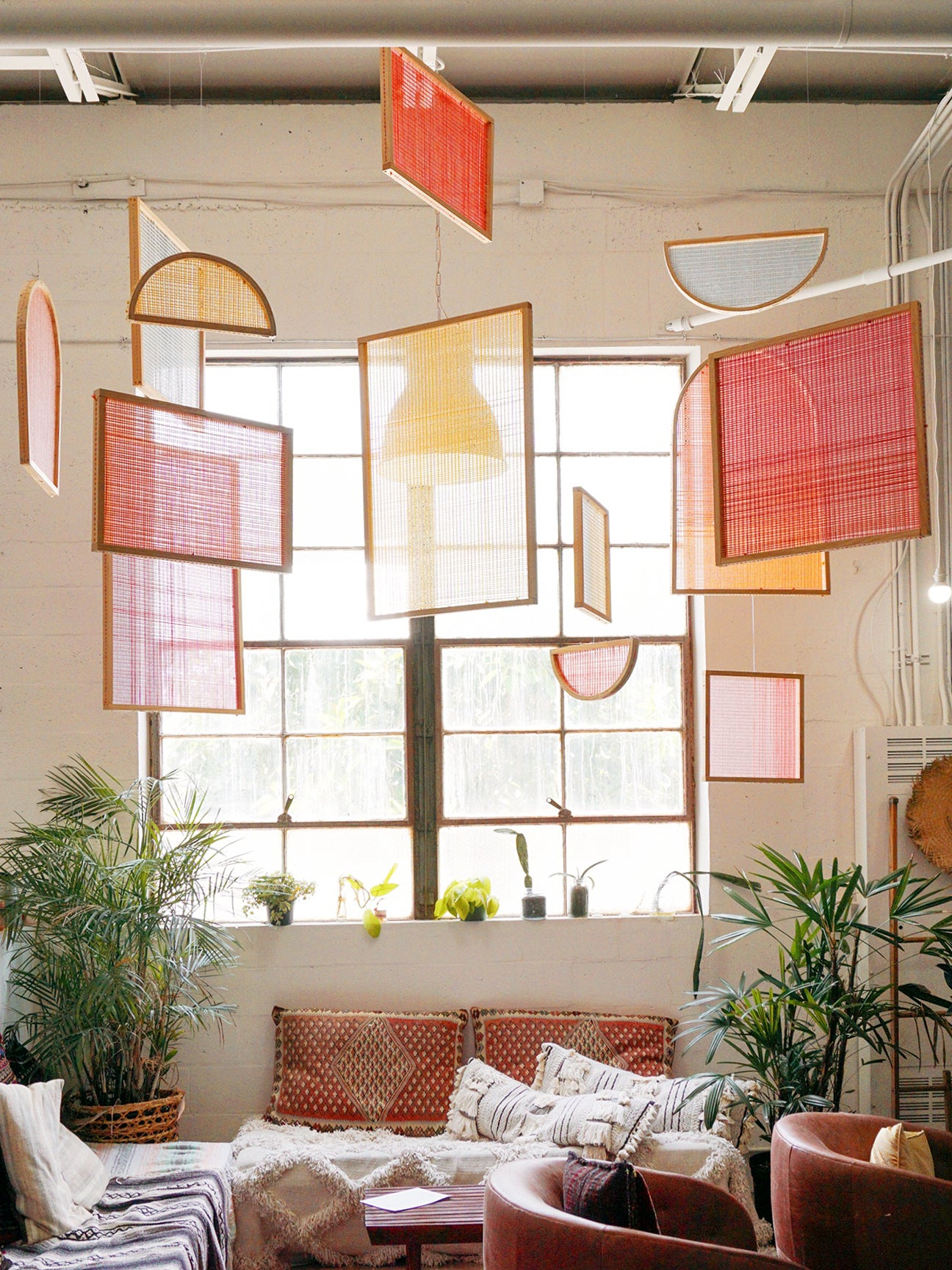 different wood frames with colorful yarn hanging from a living room ceiling