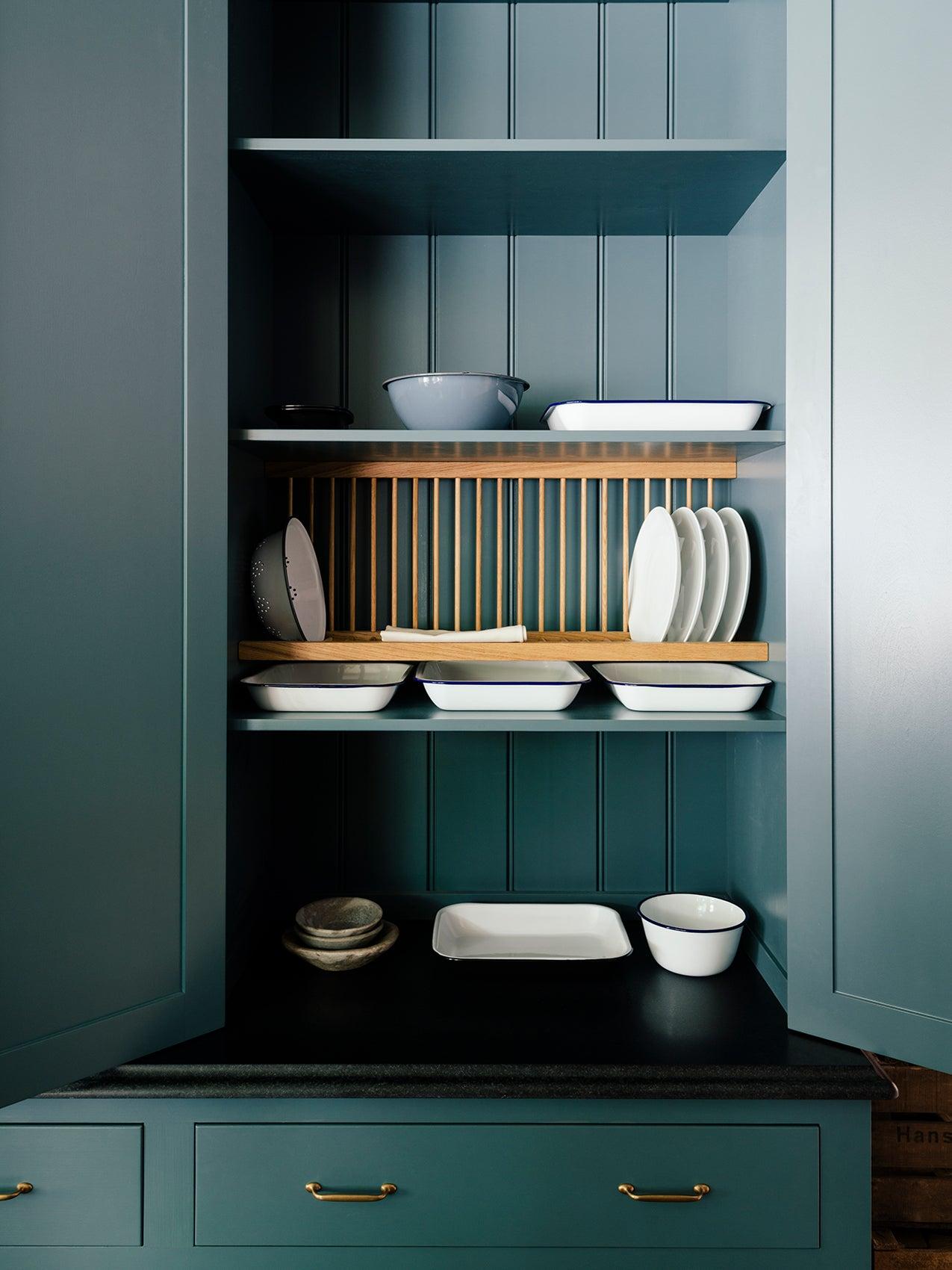 dark green open cupboard with a built in dish rack inside