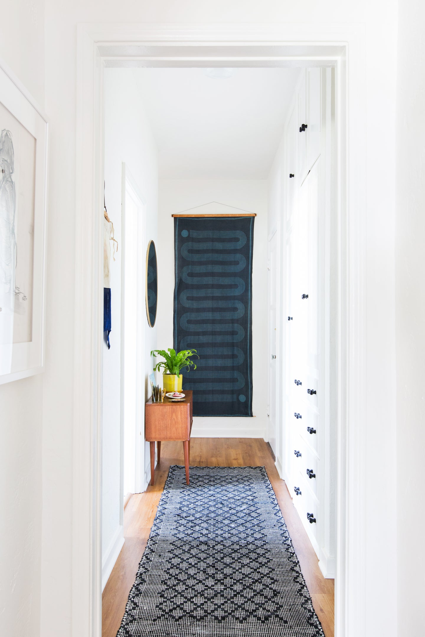 white hallway with a blue runner and blue wall hanging at the end