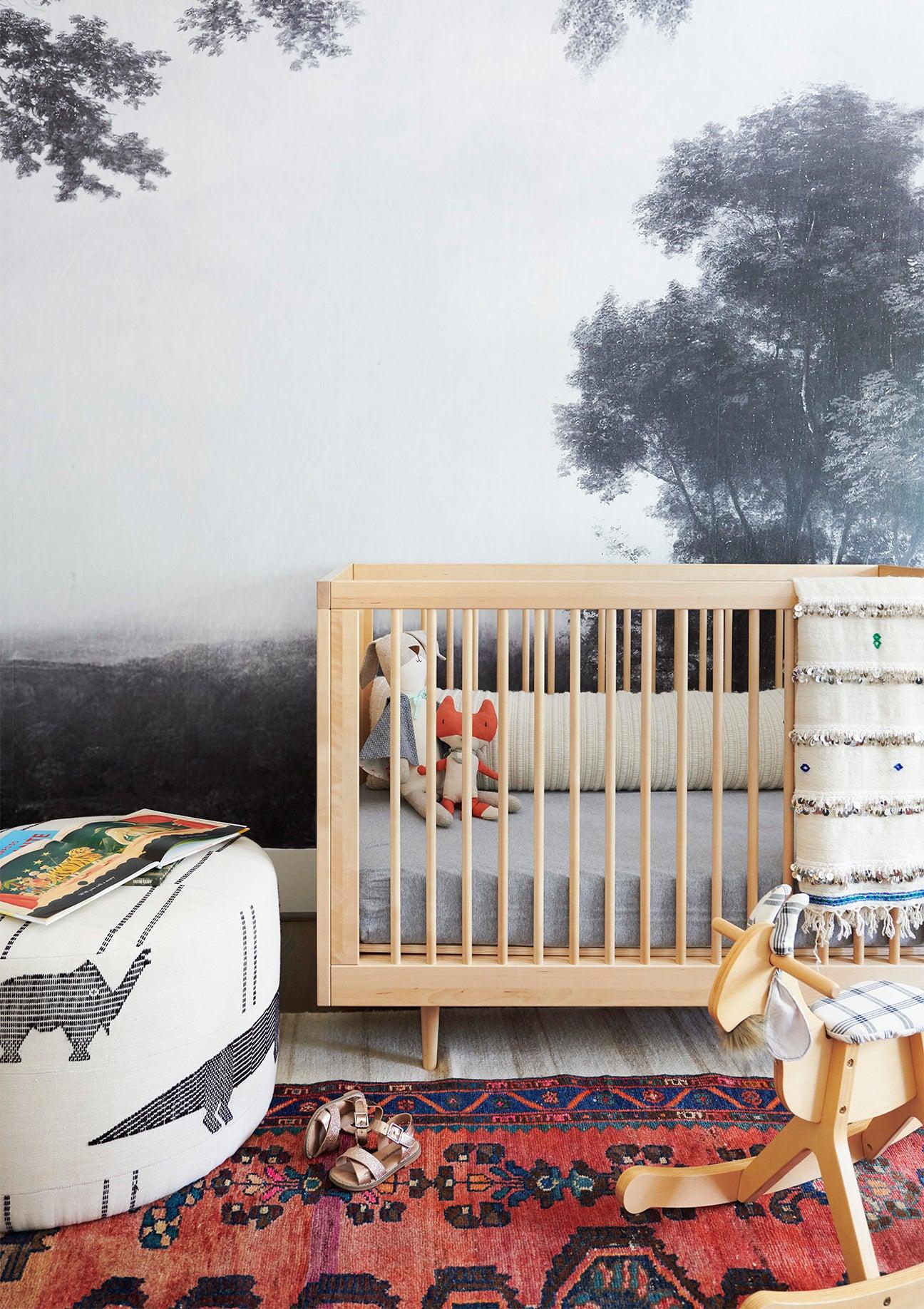 black and white jungle mural behind a wood crib