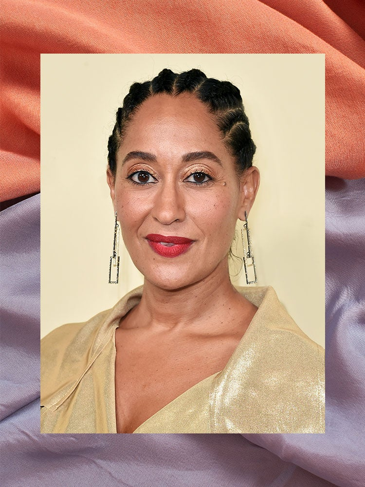 portrait of tracee ellis ross in a gold shirt with purple and red fabric border