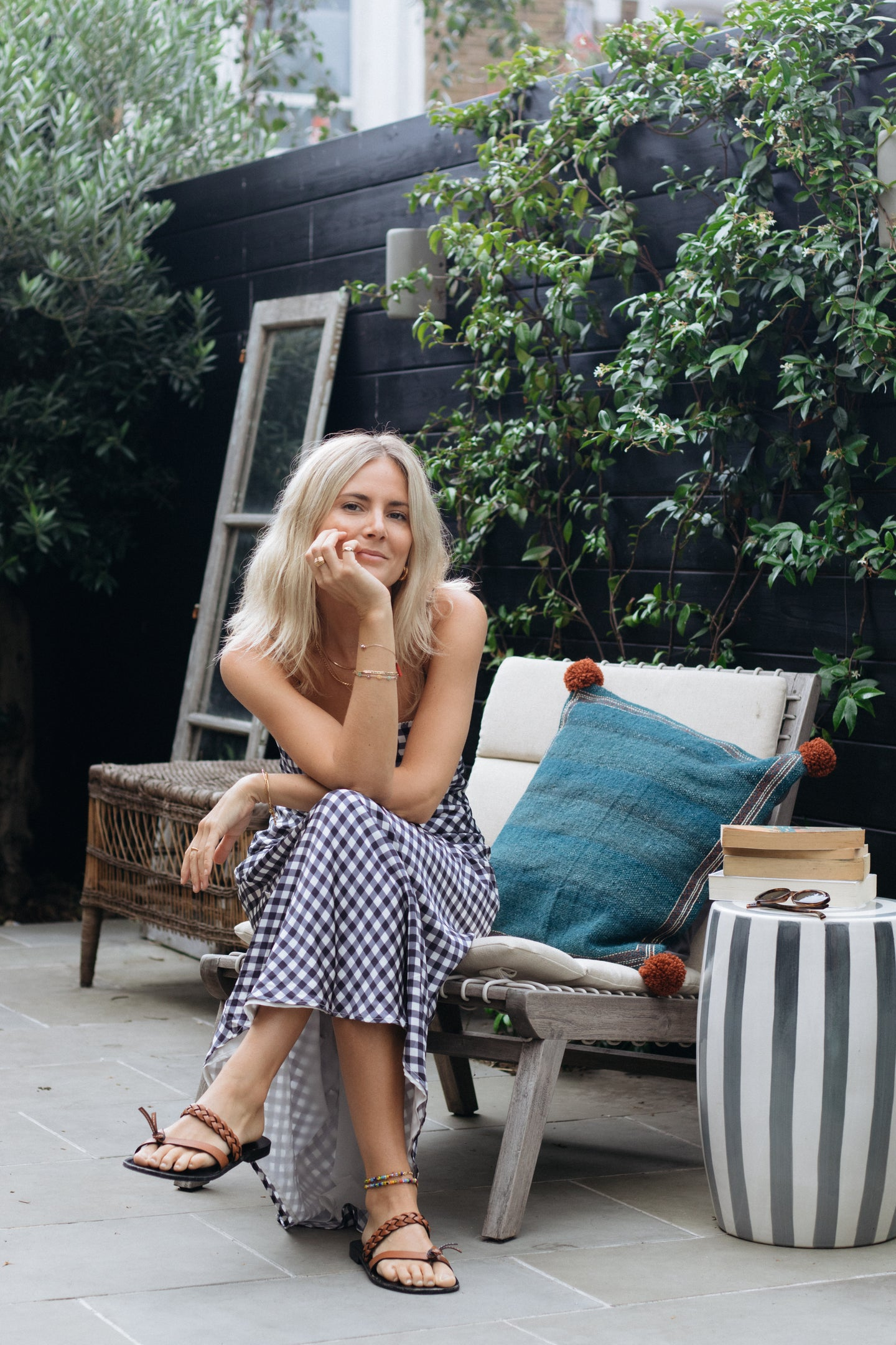 lucy williams sitting on a chair in her london backyard