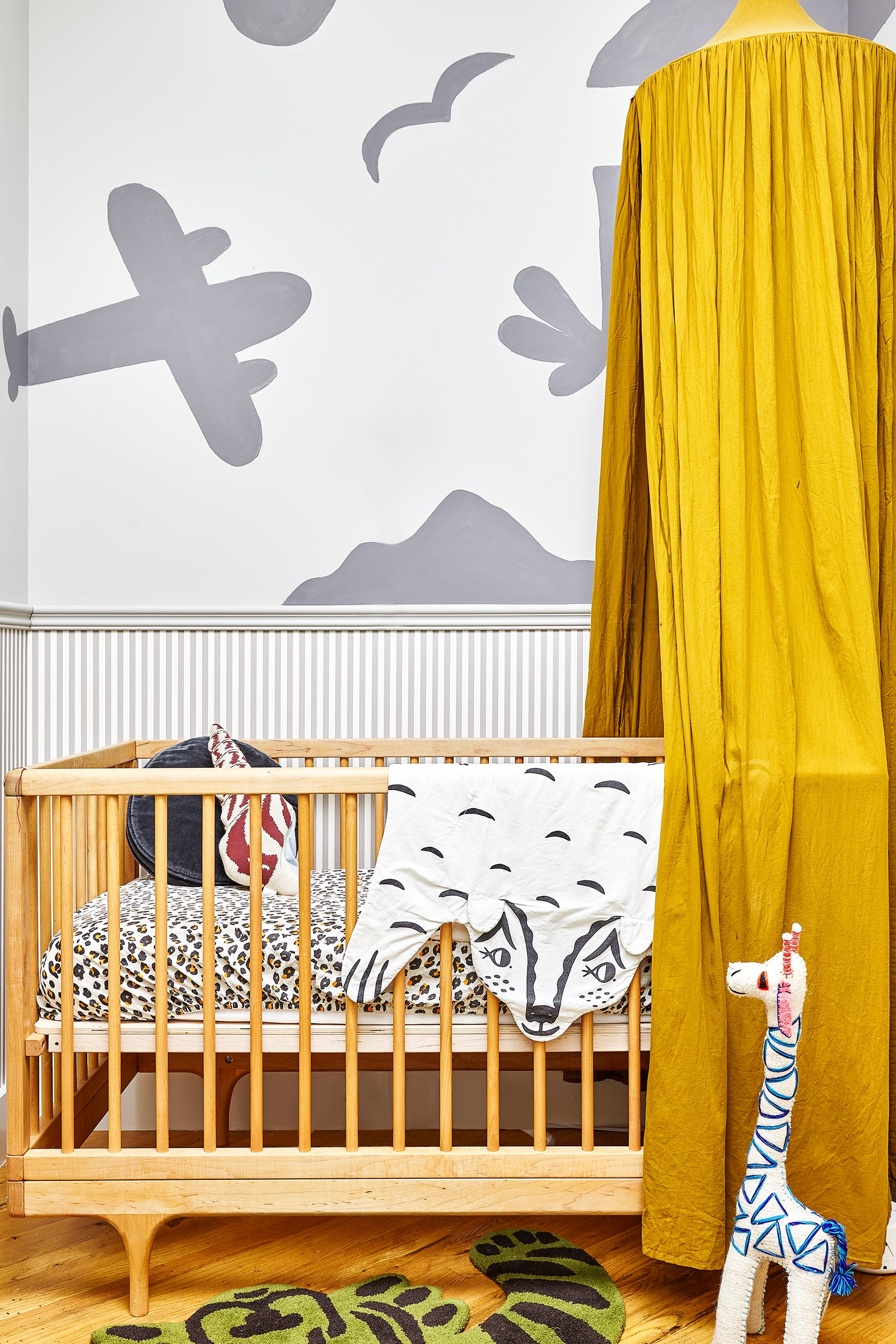 nursery crib with gray plane and mountain painted on the wall