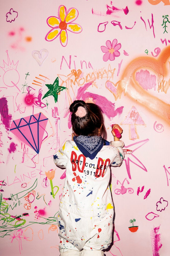 little girl scribbling on a pink wall