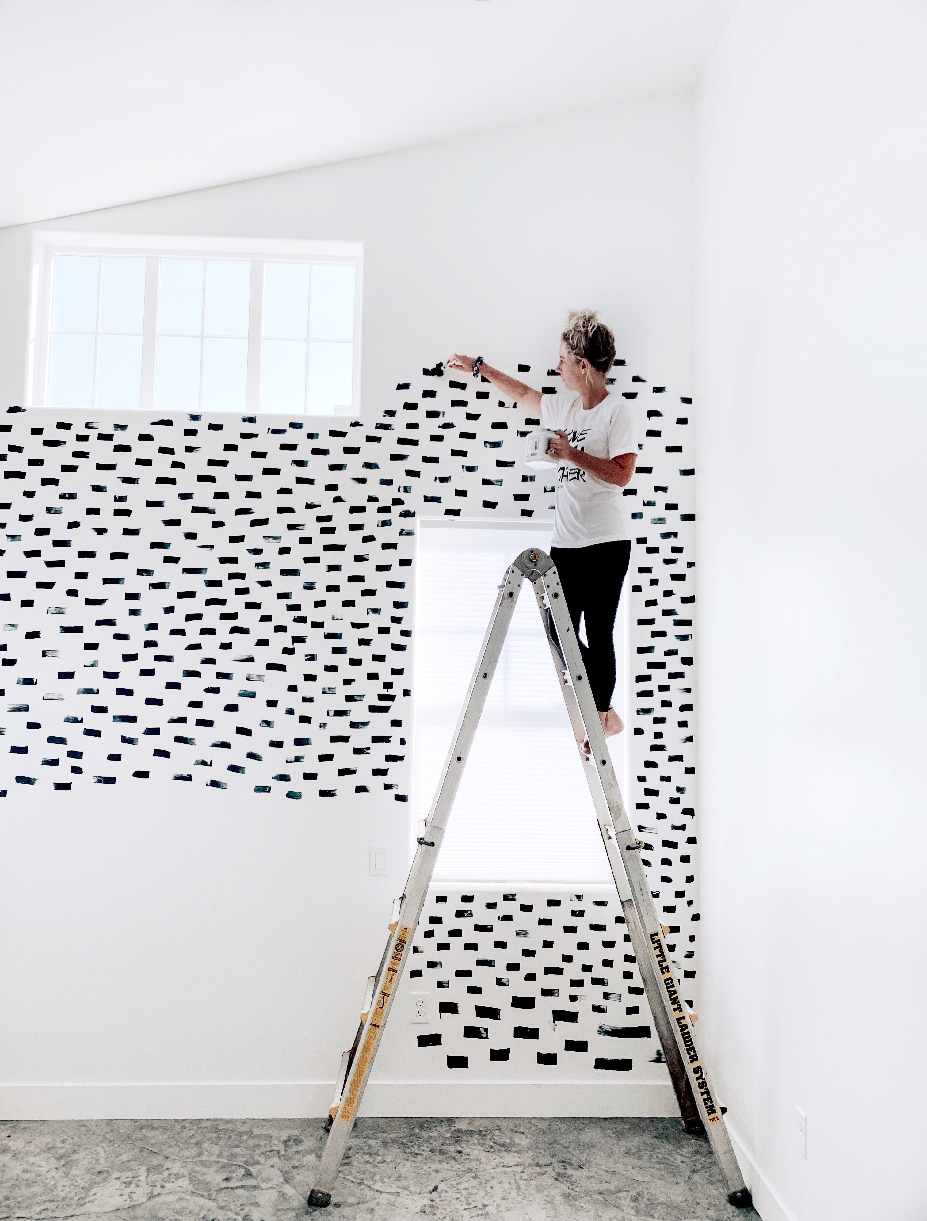 woman on a ladder painting black strokes across the wall