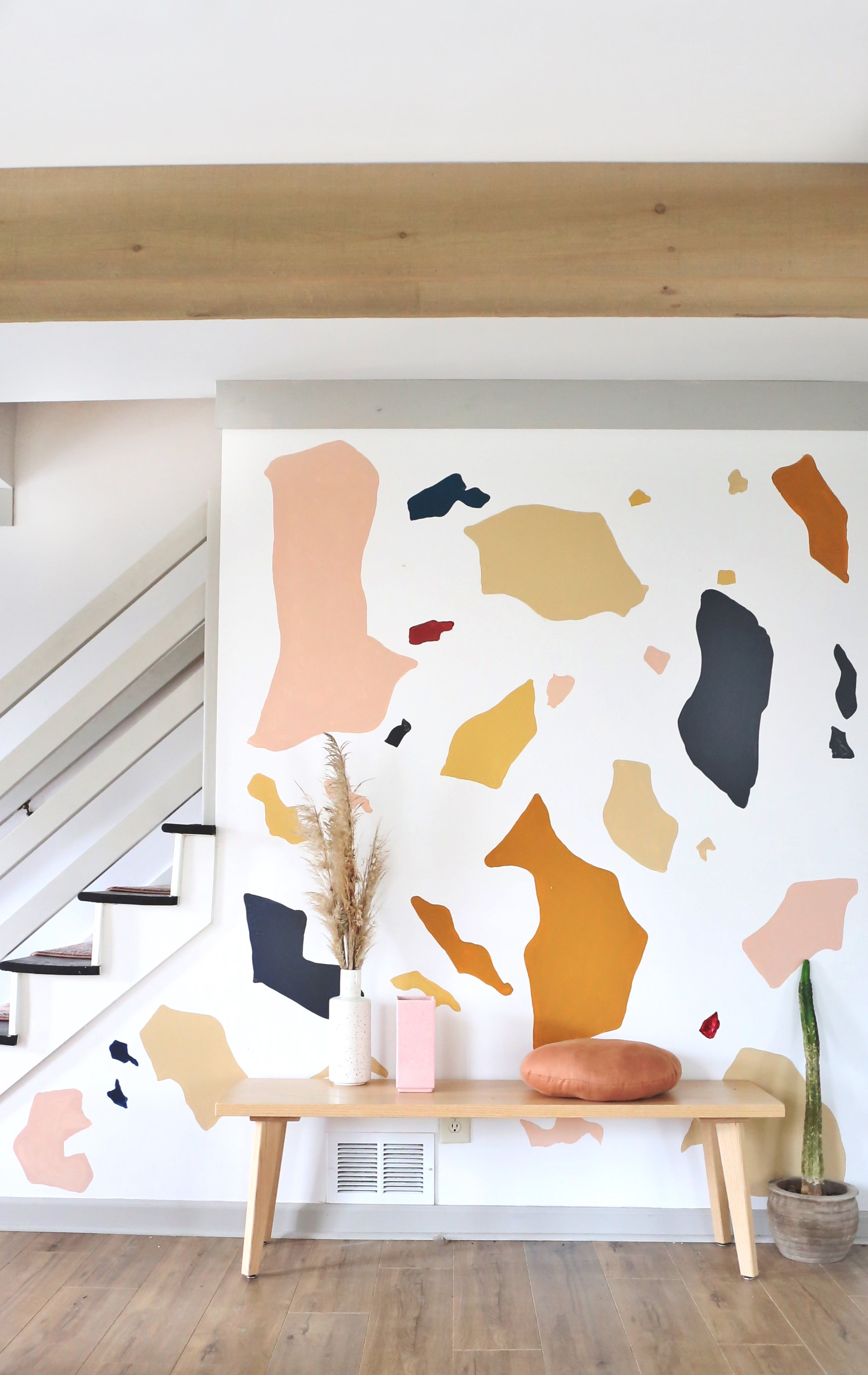 giant terrazzo shapes on a wall by the stairs