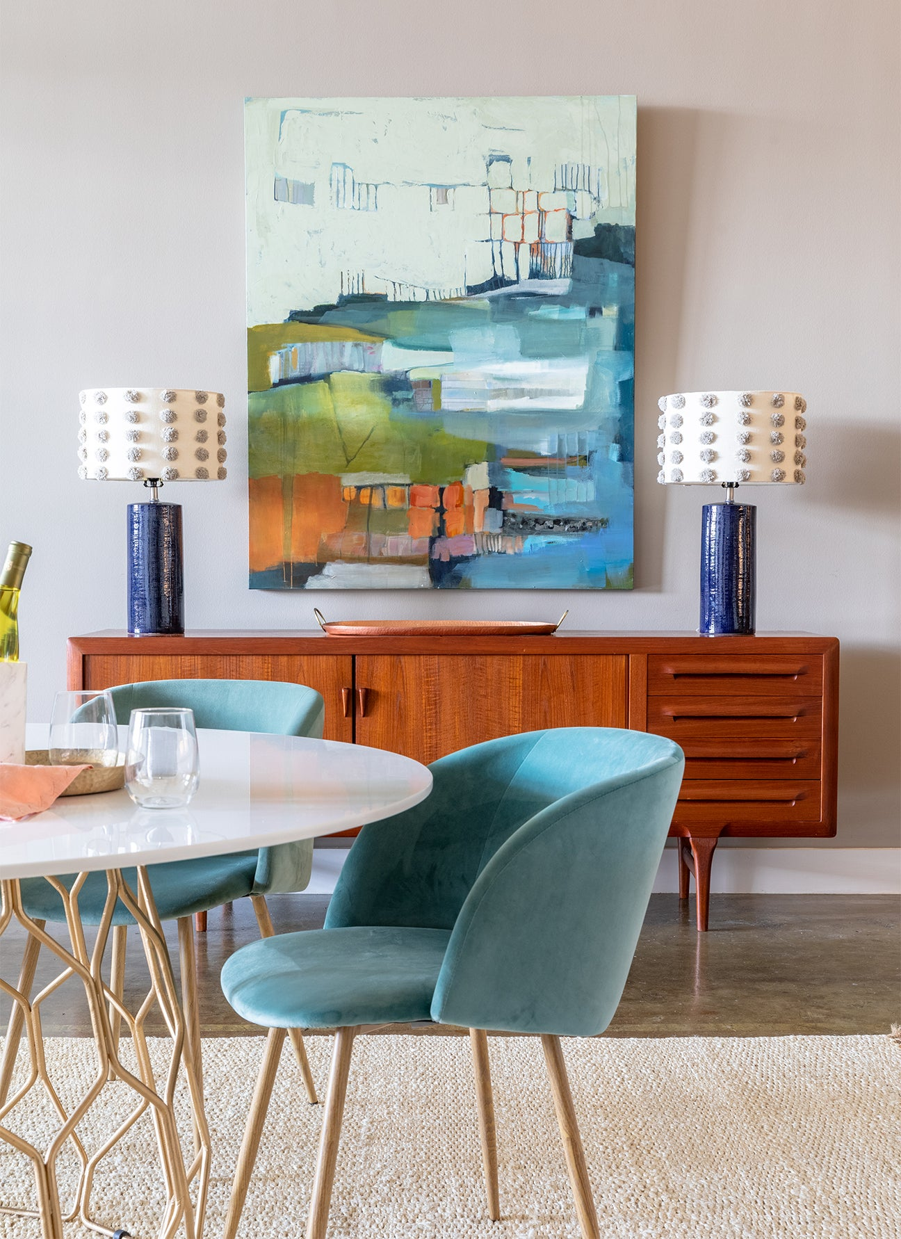 blue velvet dining room chairs with a mid century credenza in the background