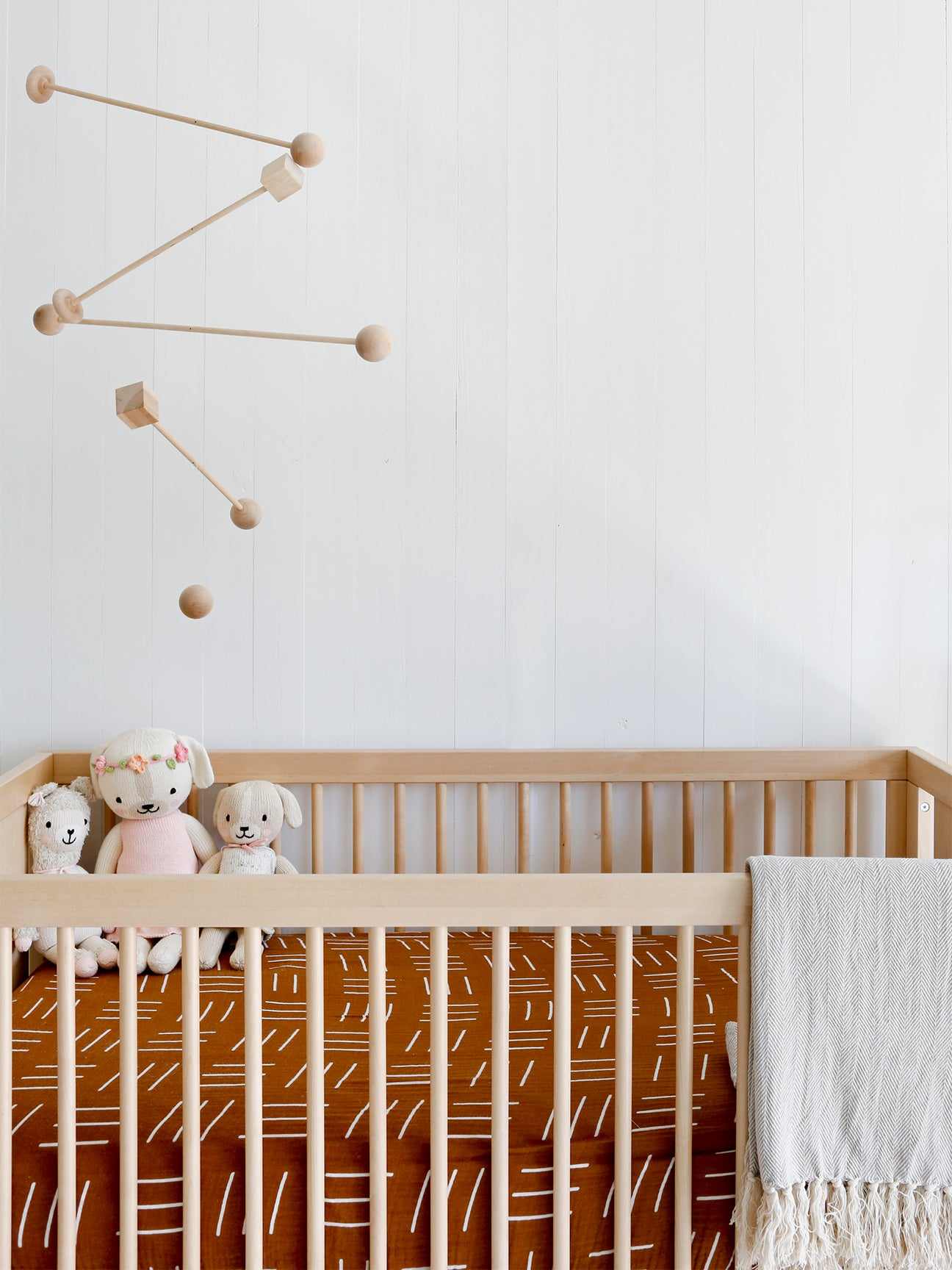 wood mobile hanging over a crib with terracotta colored sheets