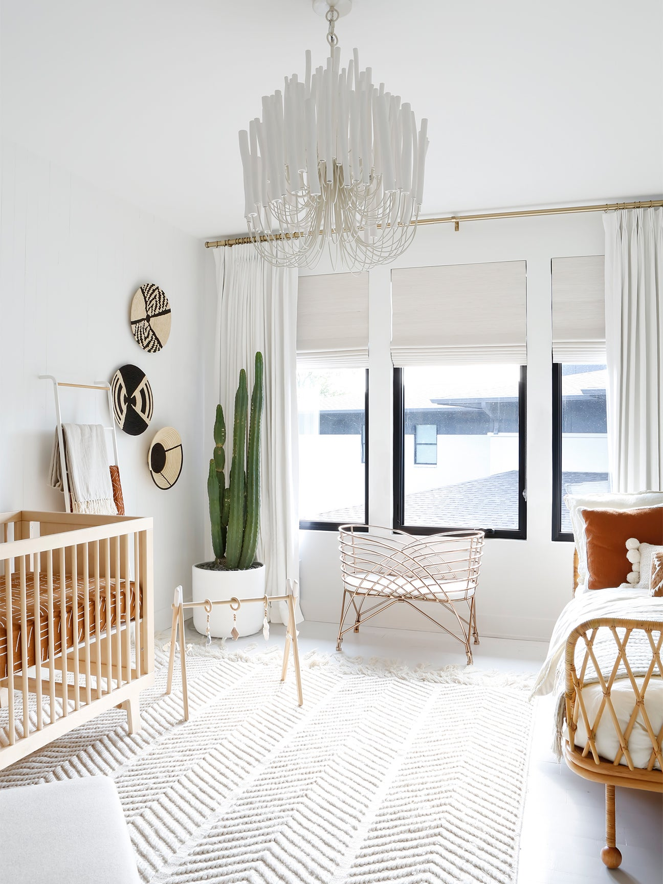 wide shot of zen, white nursery with a crib and bed