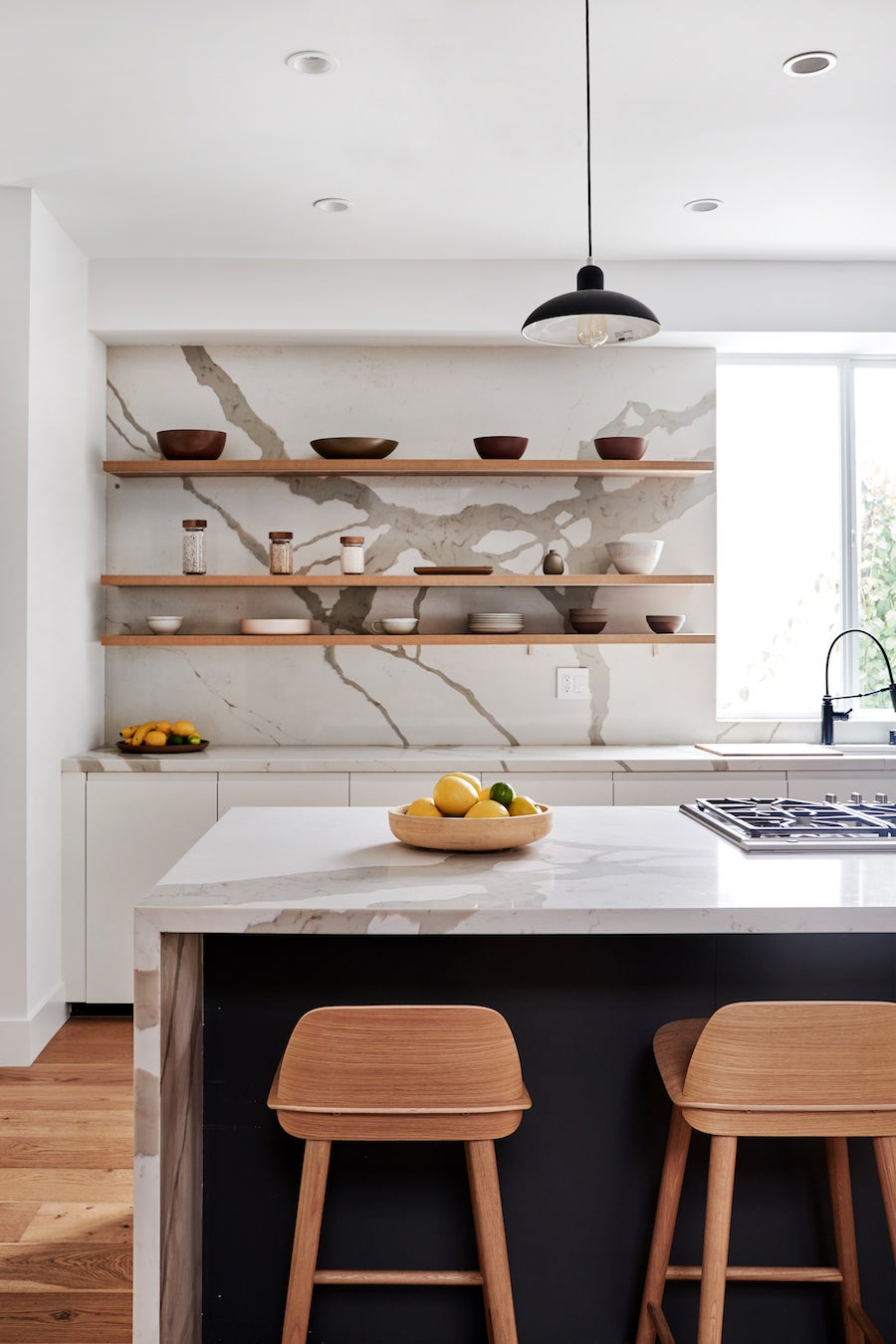 marble kitchen with slim black pendants over the island